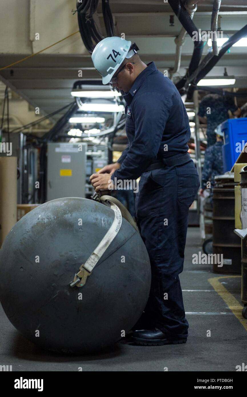 BREMERTON, Washington (July 10, 2017) Boatswain's Mate 3rd Class Bryan Diaz Padilla restows a fender inside USS John C. Stennis (CVN 74)'s hangar bay. The fender is used to create space between ships when pulling alongside one another. John C. Stennis is conducting a planned incremental availability (PIA) at Puget Sound Naval Shipyard and Intermediate Maintenance Facility, during which the ship is undergoing scheduled maintenance and upgrades. Stock Photo