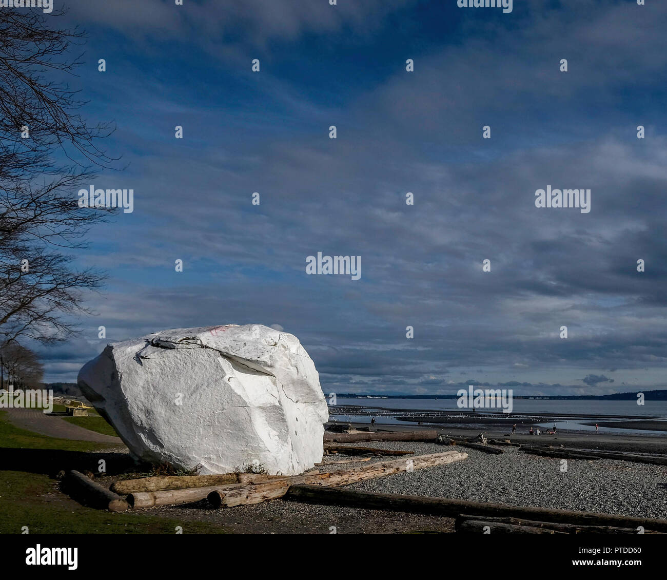 A large white rock, stoic and strong, on the beach of White Rock - Stock Image