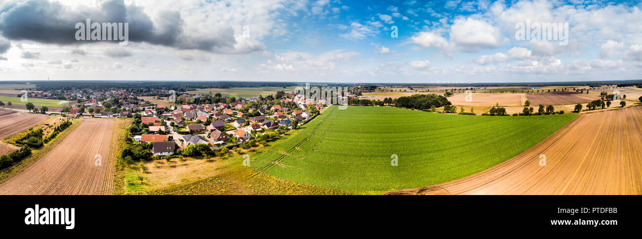 Aerial view of a small village in northern Germany with large arable land at the edge of the village. Panorama in high resolution - Stock Image
