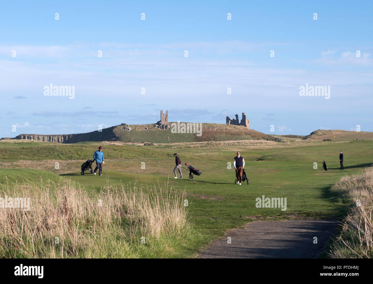 Golfers wheeling trolleys on Dunstanburgh Castle Golf Course, Northumberland, England, UK - Stock Image