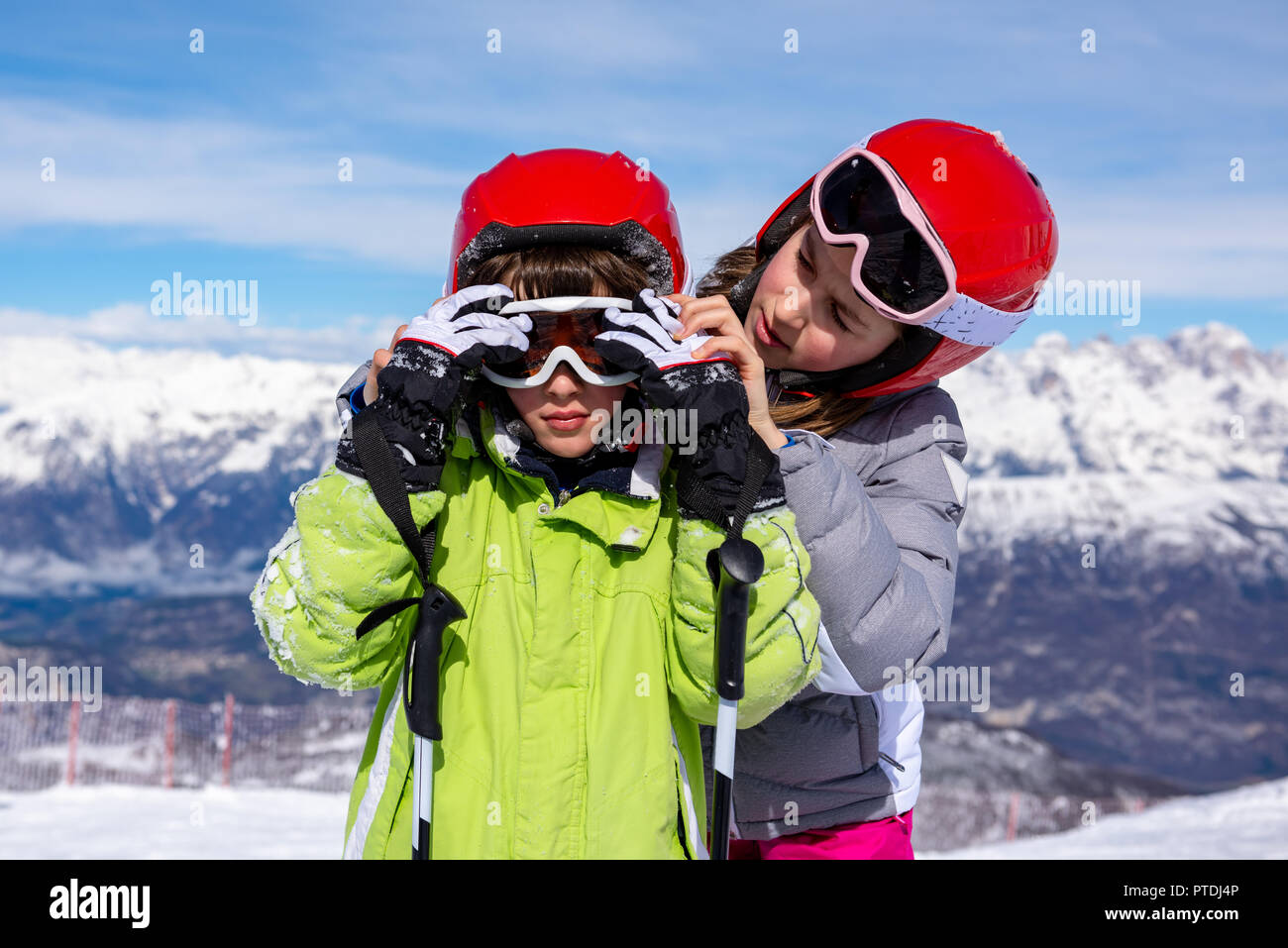 Little girl helps a child to wear ski goggles - Stock Image