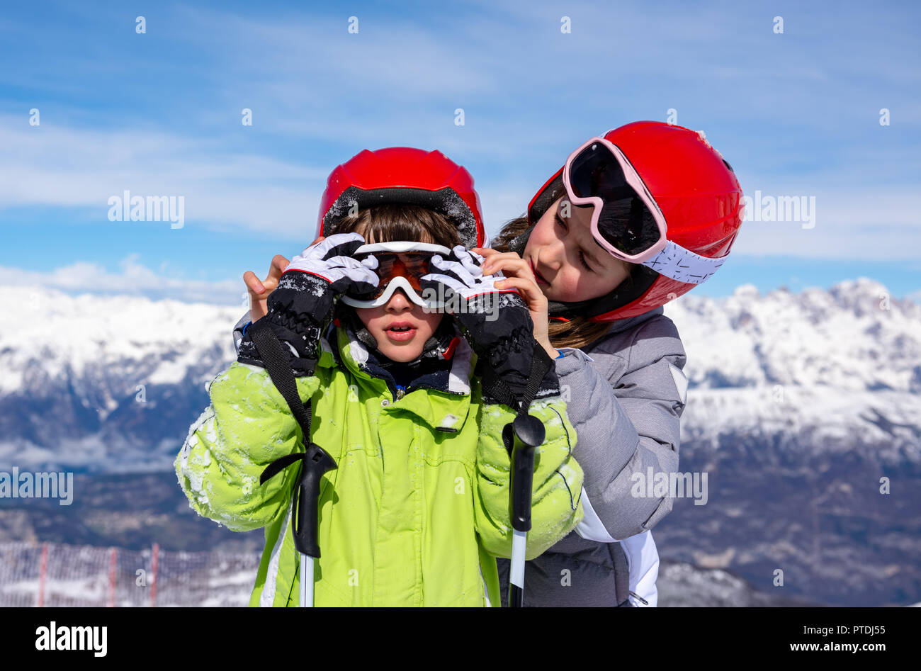 Little girl sitting in the snow wearing ski goggles - Stock Image