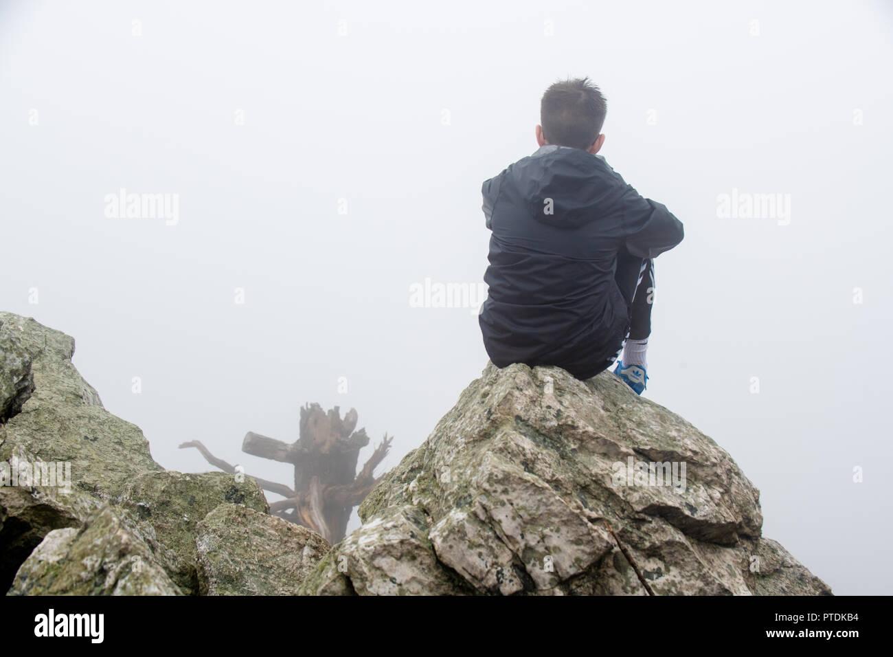 Teenager hiking / backpacking in the rain and dense fog on