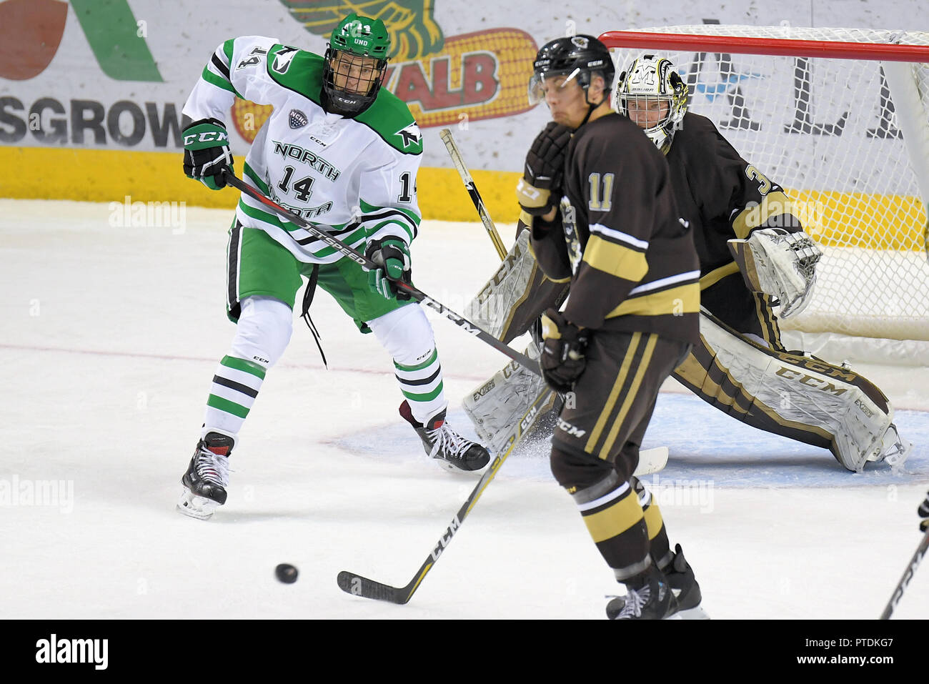 October 6, 2018 North Dakota Fighting Hawks forward Jasper Weatherby (14) watches a shot as it passes Manitoba Bisons defenseman Mitchell Dyck (11) on it's way to Manitoba Bisons goaltender Byron Spriggs (35) in the second period of an exhibition men's college hockey game between the Manitoba Bisons and the University of North Dakota Fighting Hawks at Ralph Engelstad Arena in Grand Forks. North Dakota won 3-2 in overtime. Photo by Russell Hons/CSM Stock Photo