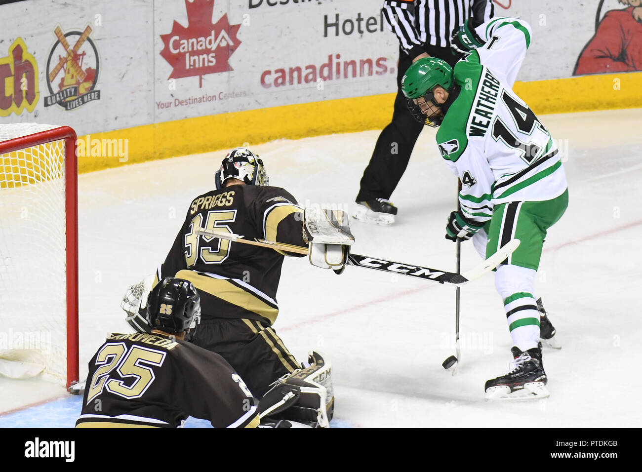 October 6, 2018 North Dakota Fighting Hawks forward Jasper Weatherby (14) attempts to shoot the puck on Manitoba Bisons goaltender Byron Spriggs (35) during an exhibition men's college hockey game between the Manitoba Bisons and the University of North Dakota Fighting Hawks at Ralph Engelstad Arena in Grand Forks. North Dakota won 3-2 in overtime. Photo by Russell Hons/CSM Stock Photo