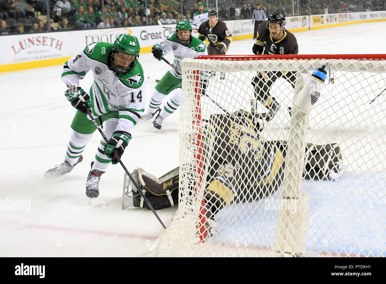 October 6, 2018 North Dakota Fighting Hawks forward Jasper Weatherby (14) tries to beat Manitoba Bisons goaltender Byron Spriggs (35) to the net in the first period of an exhibition men's college hockey game between the Manitoba Bisons and the University of North Dakota Fighting Hawks at Ralph Engelstad Arena in Grand Forks. North Dakota won 3-2 in overtime. Photo by Russell Hons/CSM - Stock Image