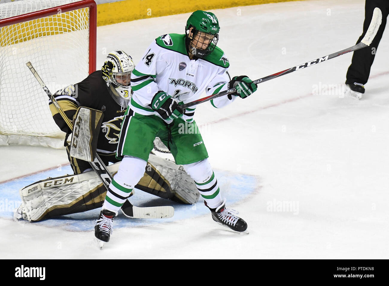 October 6, 2018 North Dakota Fighting Hawks forward Jasper Weatherby (14) takes a slapshot to the midsection in the third period of an exhibition men's college hockey game between the Manitoba Bisons and the University of North Dakota Fighting Hawks at Ralph Engelstad Arena in Grand Forks. Manitoba Bisons goaltender Byron Spriggs (35) also pictured. North Dakota won 3-2 in overtime. Photo by Russell Hons/CSM - Stock Image