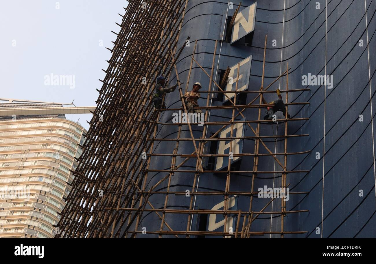 Hong Kong, CHINA. 9th Oct, 2018. Bamboo scaffoldings are being constructed along the outer wall of an old hotel awaiting to be demolished. Hong Kong preserves the classic skill of bamboo scaffolding as a Chinese traditional architectural craft. Oct-9, 2018 Hong Kong.ZUMA/Liau Chung-ren Credit: Liau Chung-ren/ZUMA Wire/Alamy Live News - Stock Image