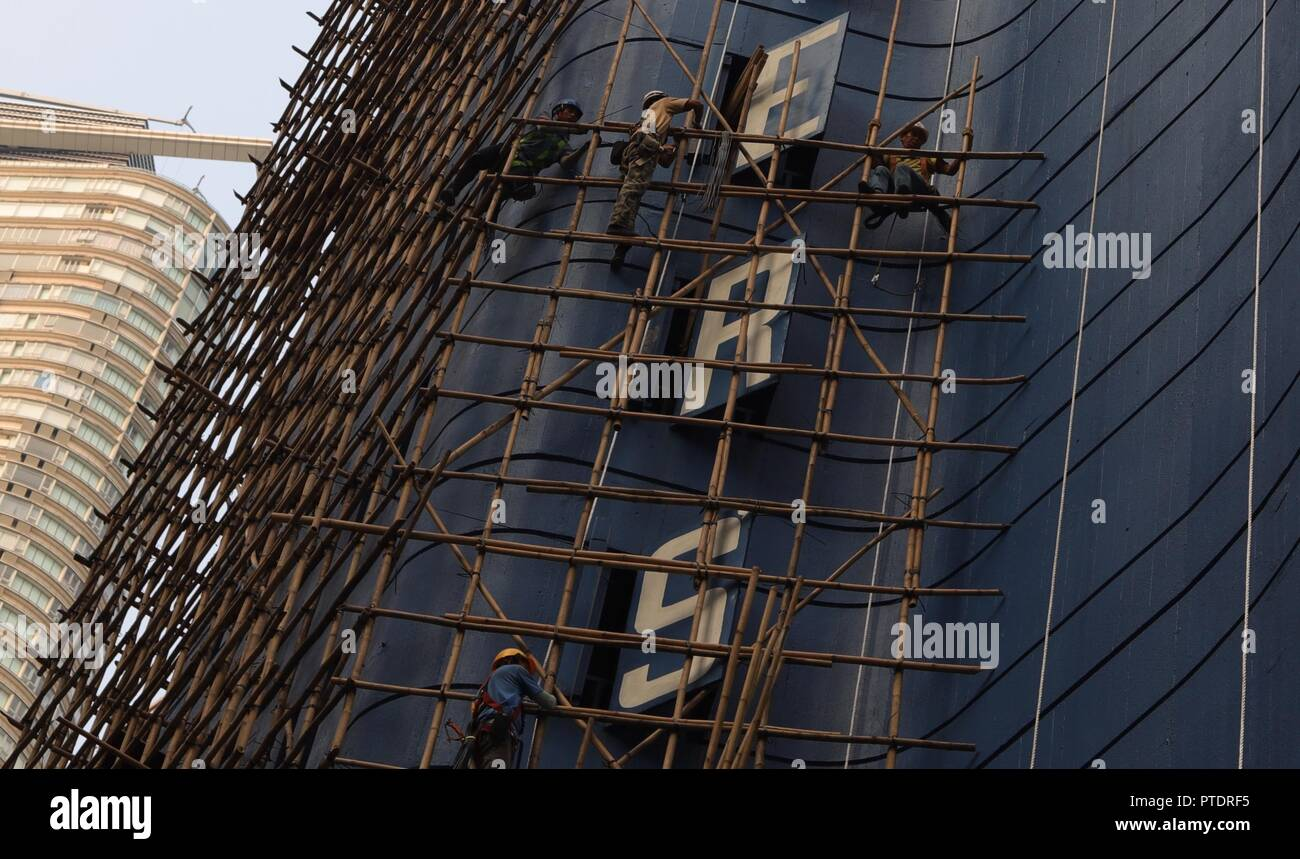 Hong Kong, CHINA. 9th Oct, 2018. Bamboo scaffolding engineers construct a bamboo scaffolding along the outer wall of an old hotel awaiting to be demolished. Hong Kong preserve classic skill of bamboo scaffoldings as a heritage of Chinese traditional architectural craft. Oct-9, 2018 Hong Kong.ZUMA/Liau Chung-ren Credit: Liau Chung-ren/ZUMA Wire/Alamy Live News - Stock Image