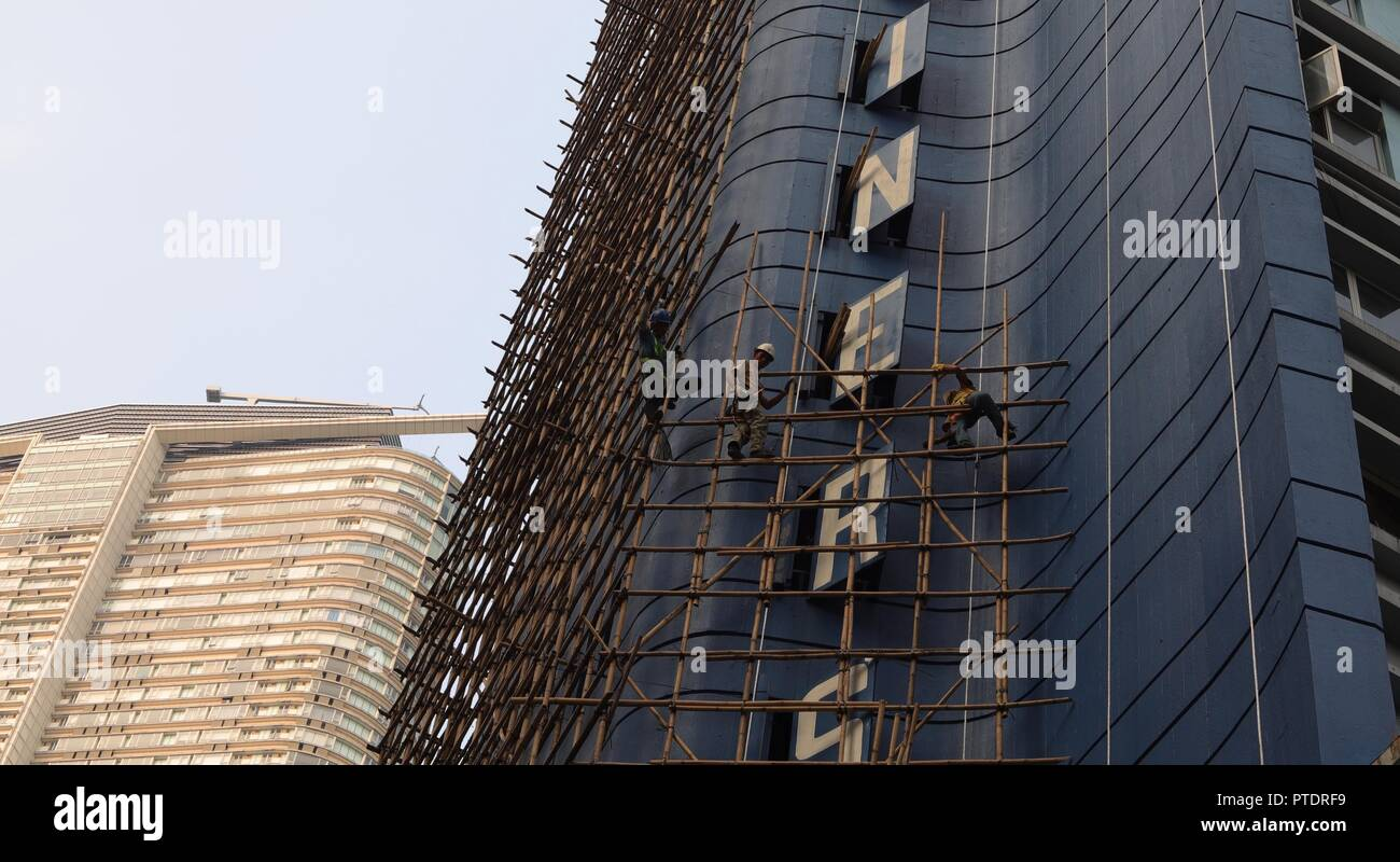 Hong Kong, CHINA. 9th Oct, 2018. A bamboo scaffolding engineers ( workers ) constructing bamboo scaffoldings along outer wall of a hotel awaiting to be demolished. Hong Kong is a place where old skill of bamboo scaffolding is kept as Chinese traditional architectural craft. Oct-9, 2018 Hong Kong.ZUMA/Liau Chung-ren Credit: Liau Chung-ren/ZUMA Wire/Alamy Live News - Stock Image