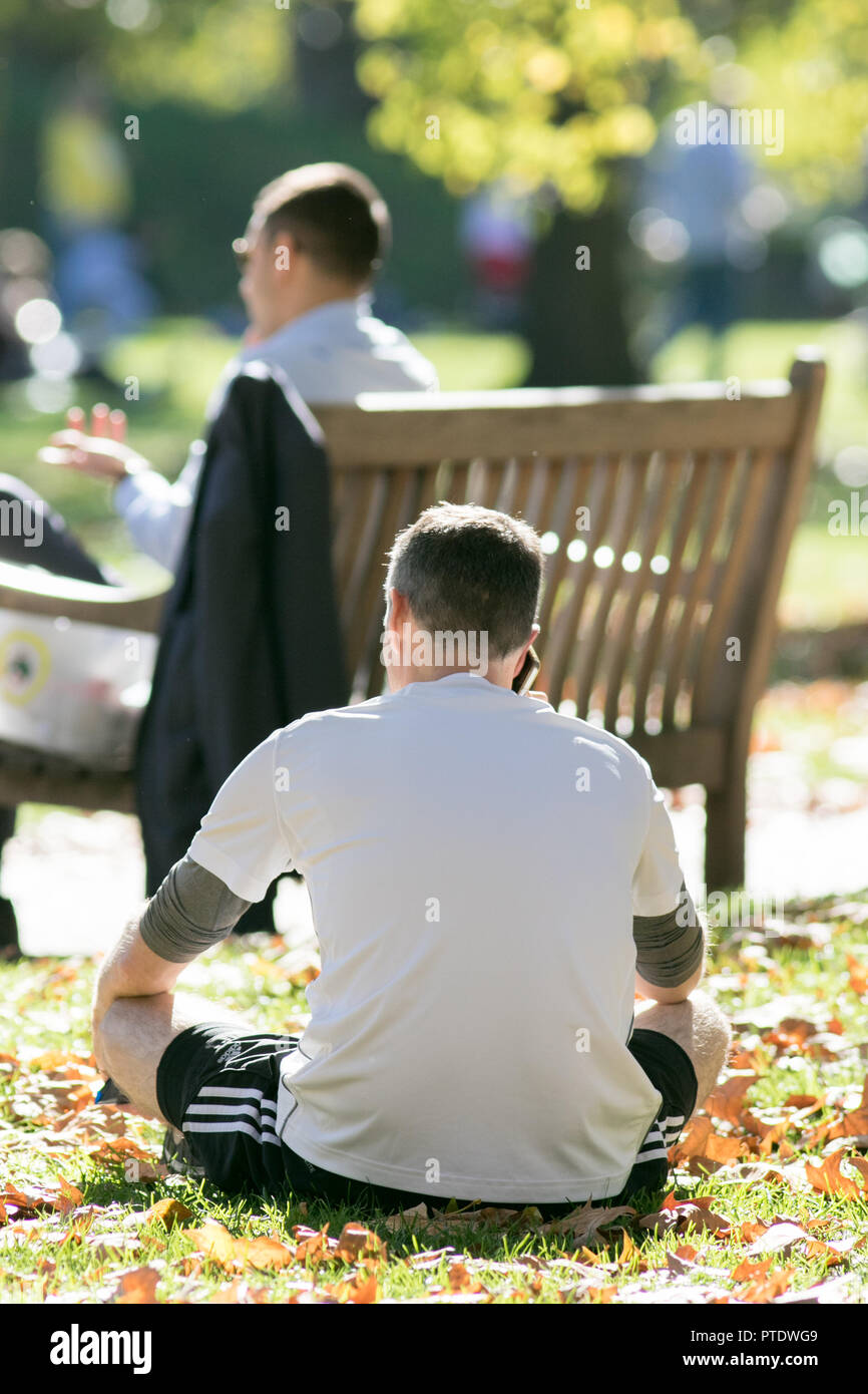 London UK. 9th Ocrober 2018. People enjoy the afternoon  sunshine in Saint James's Park covered in fallen leaves on a warm autumn day as October is forecast to be the hottest month in Seven years as the Indian summer returns Credit: amer ghazzal/Alamy Live News - Stock Image