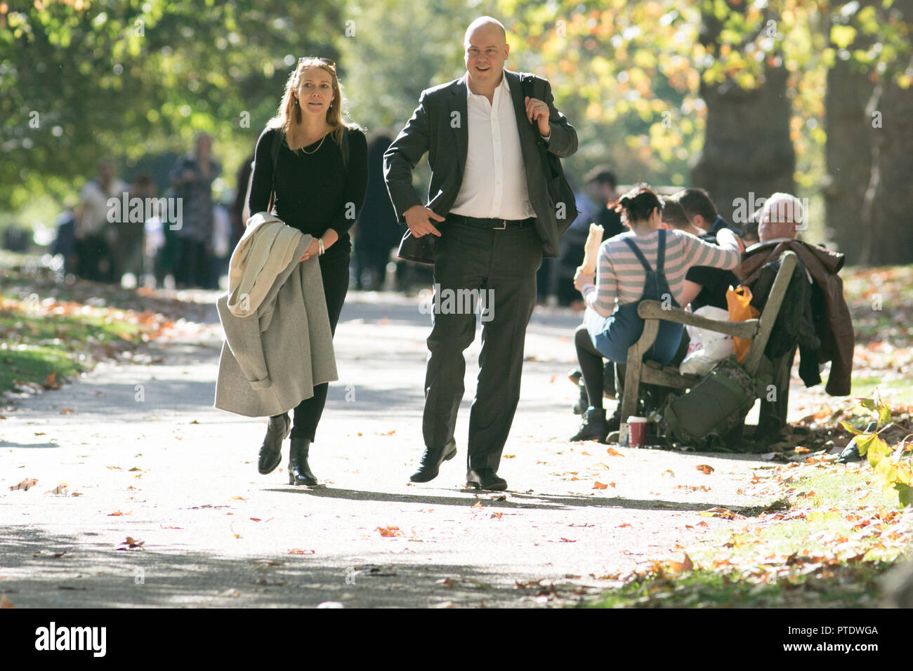 London UK. 9th Ocrober 2018. A couple  strolling in the afternoon  sunshine in Saint James's Park covered in fallen leaves on a warm autumn day as October is forecast to be the hottest month in Seven years as the Indian summer returns Credit: amer ghazzal/Alamy Live News - Stock Image