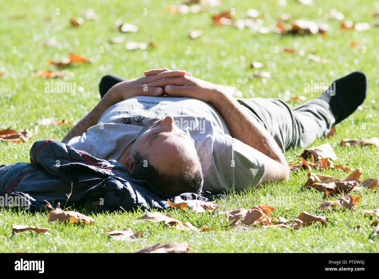 London UK. 9th Ocrober 2018. A man enjoying an nap in  the afternoon  sunshine in Saint James's Park covered in fallen leaves on a warm autumn day as October is forecast to be the hottest month in Seven years as the Indian summer returns Credit: amer ghazzal/Alamy Live News - Stock Image