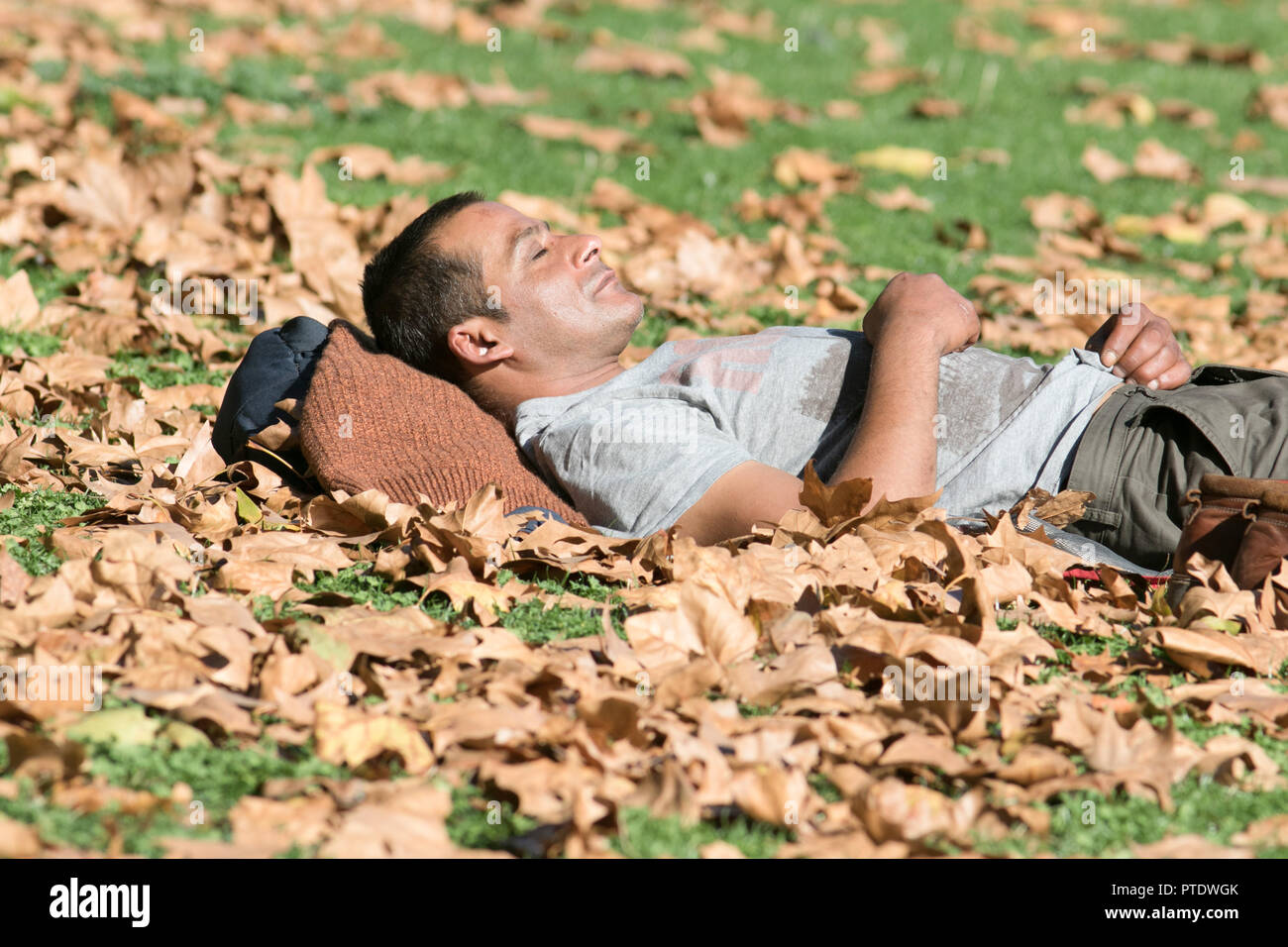 London UK. 9th October 2018. A man catching a nap in the afternoon sunshine on the park grass covered with autumn leaves  in Saint James's Park Credit: amer ghazzal/Alamy Live News - Stock Image
