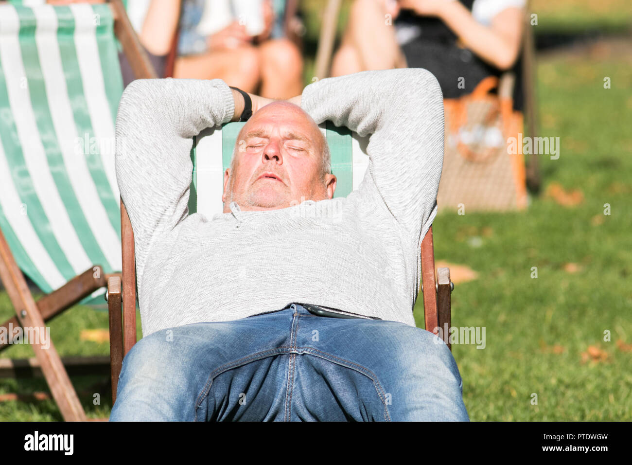 London UK. 9th Ocrober 2018. A man catching a nap in   the afternoon  sunshine in Saint James's Park covered in fallen leaves on a warm autumn day as October is forecast to be the hottest month in Seven years as the Indian summer returns Credit: amer ghazzal/Alamy Live News - Stock Image