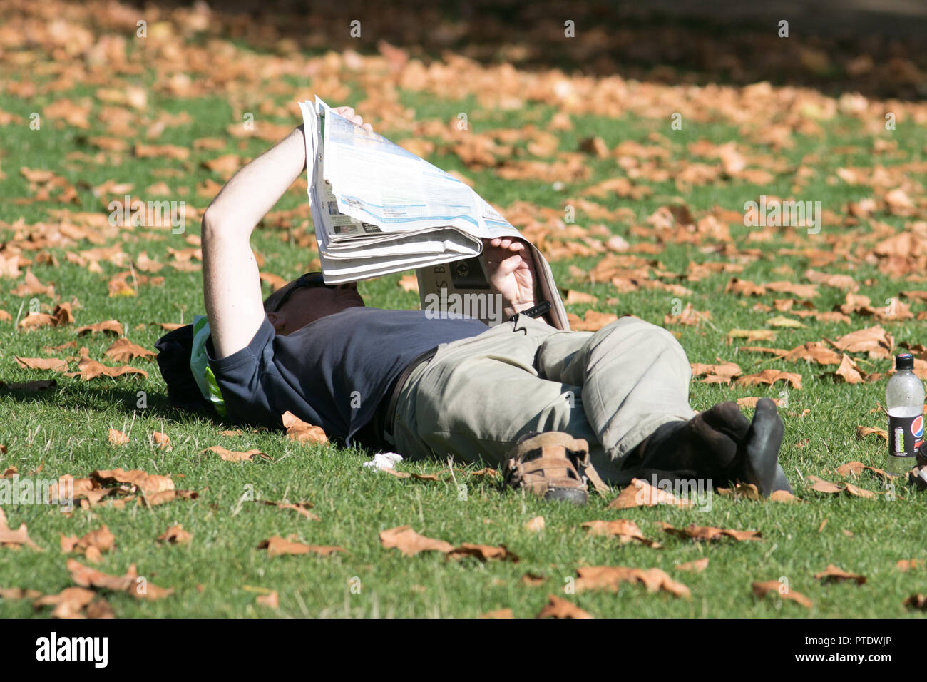 London UK. 9th Ocrober 2018.a man reading a newspaper on the grass  in the afternoon  sunshine in Saint James's Park covered in fallen leaves on a warm autumn day as October is forecast to be the hottest month in Seven years as the Indian summer returns Credit: amer ghazzal/Alamy Live News - Stock Image
