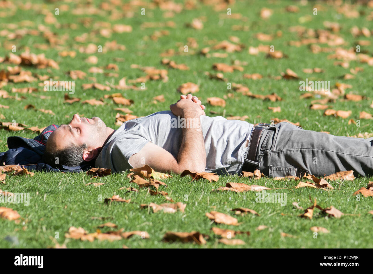 London UK. 9th Ocrober 2018. People snoozing and sunbathing in the afternoon  sunshine in Saint James's Park covered in fallen leaves on a warm autumn day as October is forecast to be the hottest month in Seven years as the Indian summer returns Credit: amer ghazzal/Alamy Live News - Stock Image