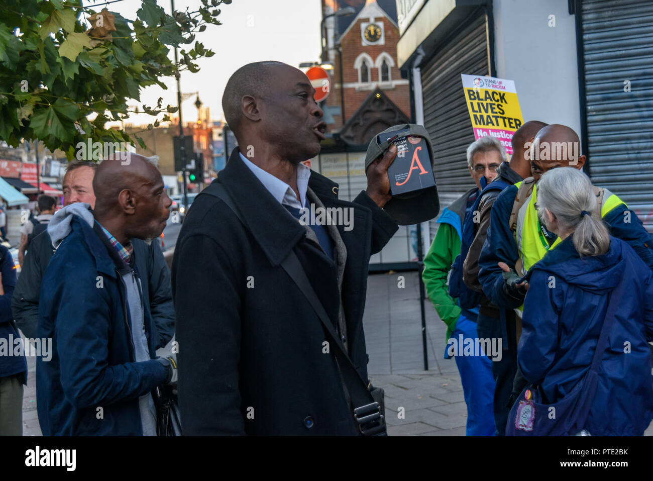 London, UK. October 9th 2018. A man complains about his treatment by police and the justice system as people gather for a rally outside the New Atlas Cafe Restaurant where a young black man was attacked by police who used obviously unnecessary force when arresting him on suspicion of having been involved in a knife attack. He was assaulted by six officers, and was viciously kicked while officers struggled to handcuff him, andwhen he was well under control and held on the ground he was sprayed in the face with CS gas. Credit: Peter Marshall/Alamy Live News - Stock Image
