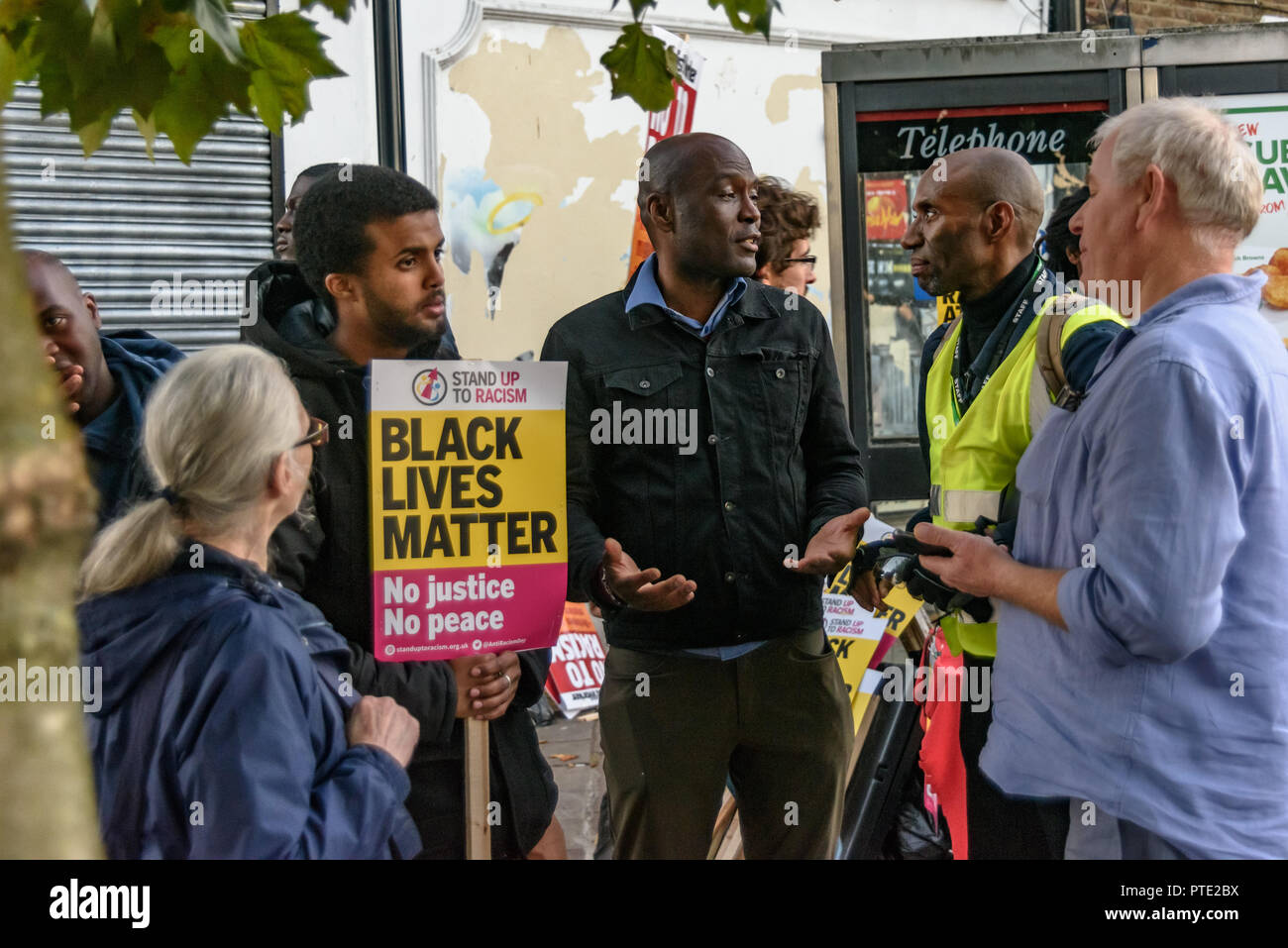 London, UK. October 9th 2018. People hold an animated discussion as they gather for a rally outside the New Atlas Cafe Restaurant where a young black man was attacked by police who used obviously unnecessary force when arresting him on suspicion of having been involved in a knife attack. He was assaulted by six officers, and was viciously kicked while officers struggled to handcuff him, andwhen he was well under control and held on the ground he was sprayed in the face with CS gas. Credit: Peter Marshall/Alamy Live News - Stock Image