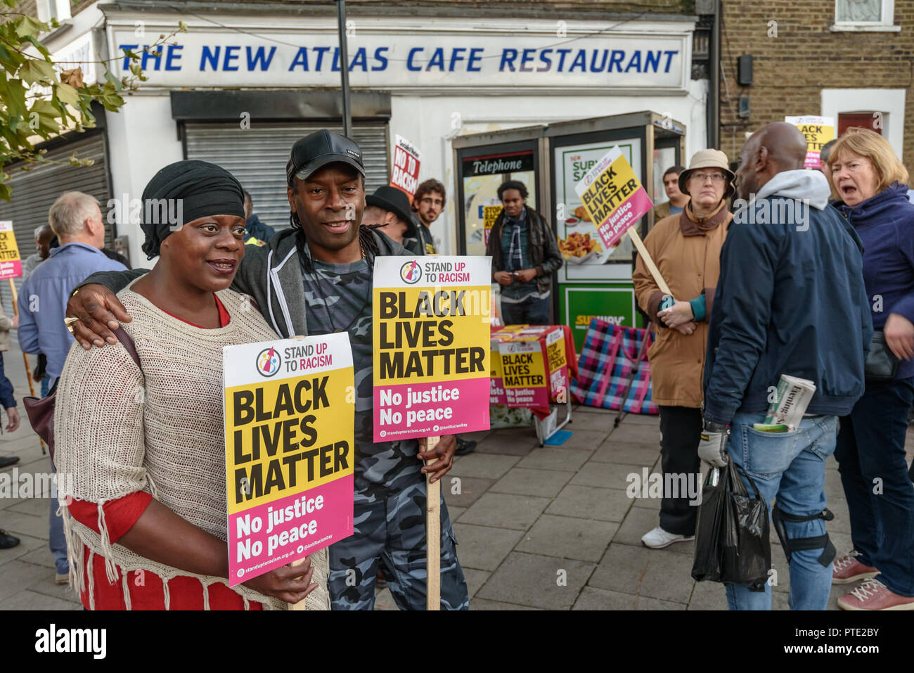 London, UK. October 9th 2018. People gather for a rally outside the New Atlas Cafe Restaurant where a young black man was attacked by police who used obviously unnecessary force when arresting him on suspicion of having been involved in a knife attack. He was assaulted by six officers, and was viciously kicked while officers struggled to handcuff him, andwhen he was well under control and held on the ground he was sprayed in the face with CS gas. Credit: Peter Marshall/Alamy Live News - Stock Image