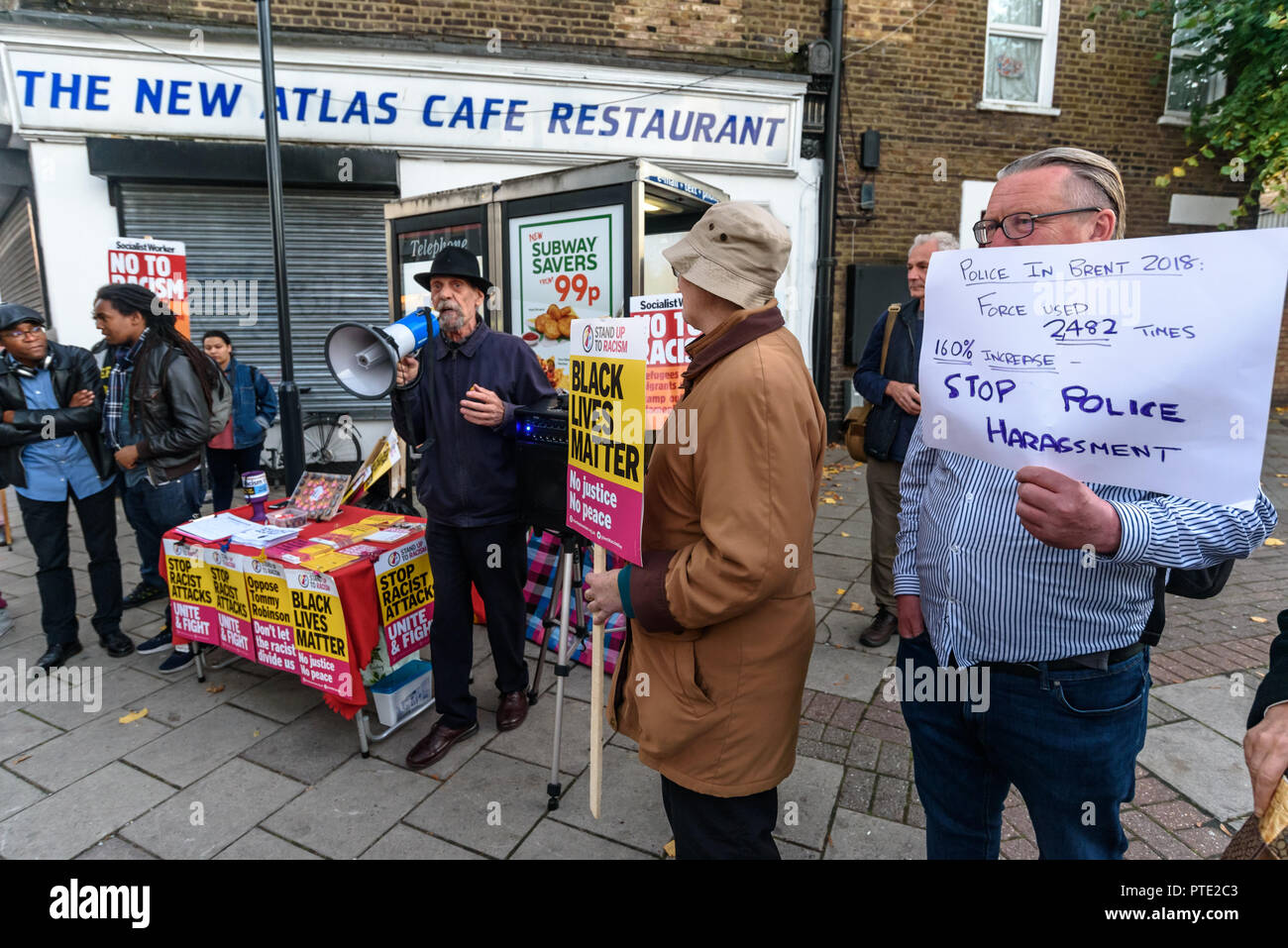 London, UK. October 9th 2018. A man holds up a poster showing a huge increase in police use of force in Brent at the rally outside the New Atlas Cafe Restaurant where a young black man was attacked by police who used obviously unnecessary force when arresting him on suspicion of having been involved in a knife attack. He was assaulted by six officers, and was viciously kicked while officers struggled to handcuff him, andwhen he was well under control and held on the ground he was sprayed in the face with CS gas. Credit: Peter Marshall/Alamy Live News - Stock Image
