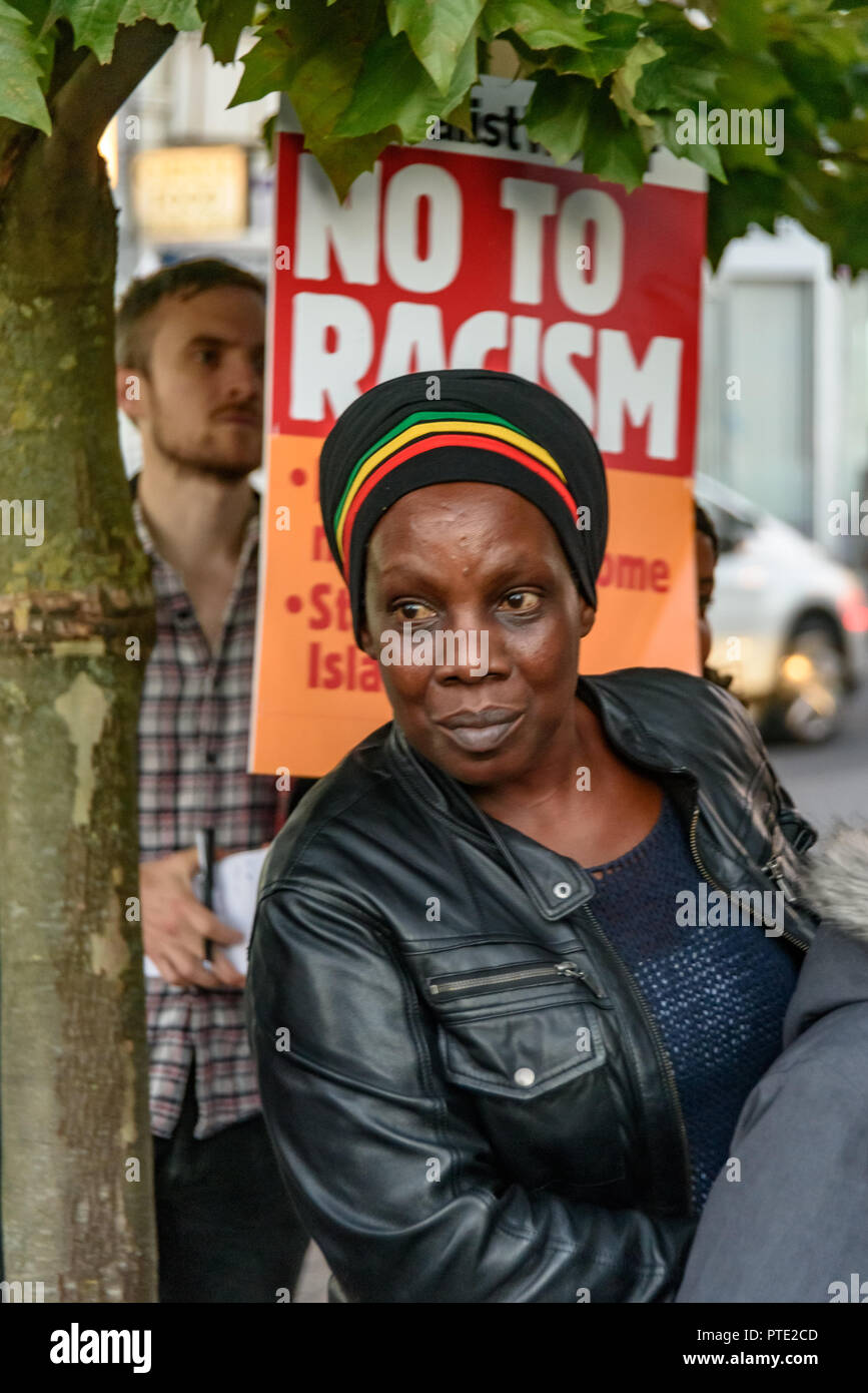 London, UK. October 9th 2018. A woman at the rally outside the New Atlas Cafe Restaurant where a young black man was attacked by police who used obviously unnecessary force when arresting him on suspicion of having been involved in a knife attack. He was assaulted by six officers, and was viciously kicked while officers struggled to handcuff him, andwhen he was well under control and held on the ground he was sprayed in the face with CS gas. Credit: Peter Marshall/Alamy Live News - Stock Image