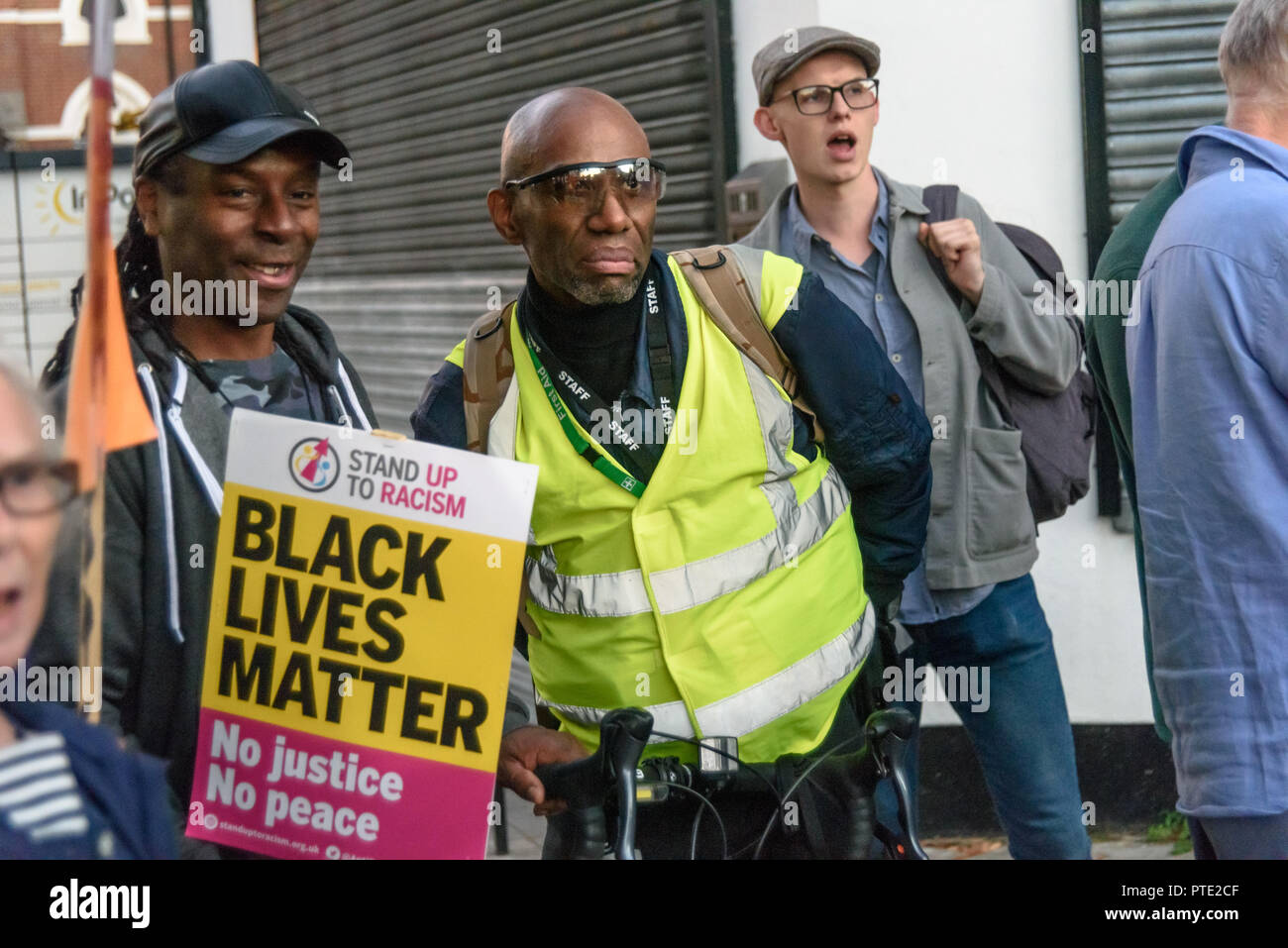 London, UK. October 9th 2018. People at the  rally outside the New Atlas Cafe Restaurant where a young black man was attacked by police who used obviously unnecessary force when arresting him on suspicion of having been involved in a knife attack. He was assaulted by six officers, and was viciously kicked while officers struggled to handcuff him, andwhen he was well under control and held on the ground he was sprayed in the face with CS gas. Credit: Peter Marshall/Alamy Live News - Stock Image