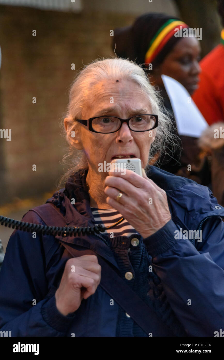 London, UK. October 9th 2018. A woman who taught for many years in the area speaks at the rally outside the New Atlas Cafe Restaurant where a young black man was attacked by police who used obviously unnecessary force when arresting him on suspicion of having been involved in a knife attack. He was assaulted by six officers, and was viciously kicked while officers struggled to handcuff him, andwhen he was well under control and held on the ground he was sprayed in the face with CS gas. Credit: Peter Marshall/Alamy Live News - Stock Image
