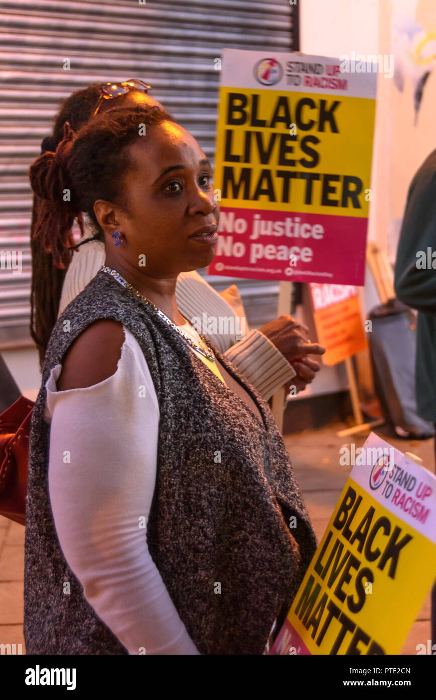 London, UK. October 9th 2018.Women listen at the rally outside the New Atlas Cafe Restaurant where a young black man was attacked by police who used obviously unnecessary force when arresting him on suspicion of having been involved in a knife attack. He was assaulted by six officers, and was viciously kicked while officers struggled to handcuff him, andwhen he was well under control and held on the ground he was sprayed in the face with CS gas. Credit: Peter Marshall/Alamy Live News - Stock Image
