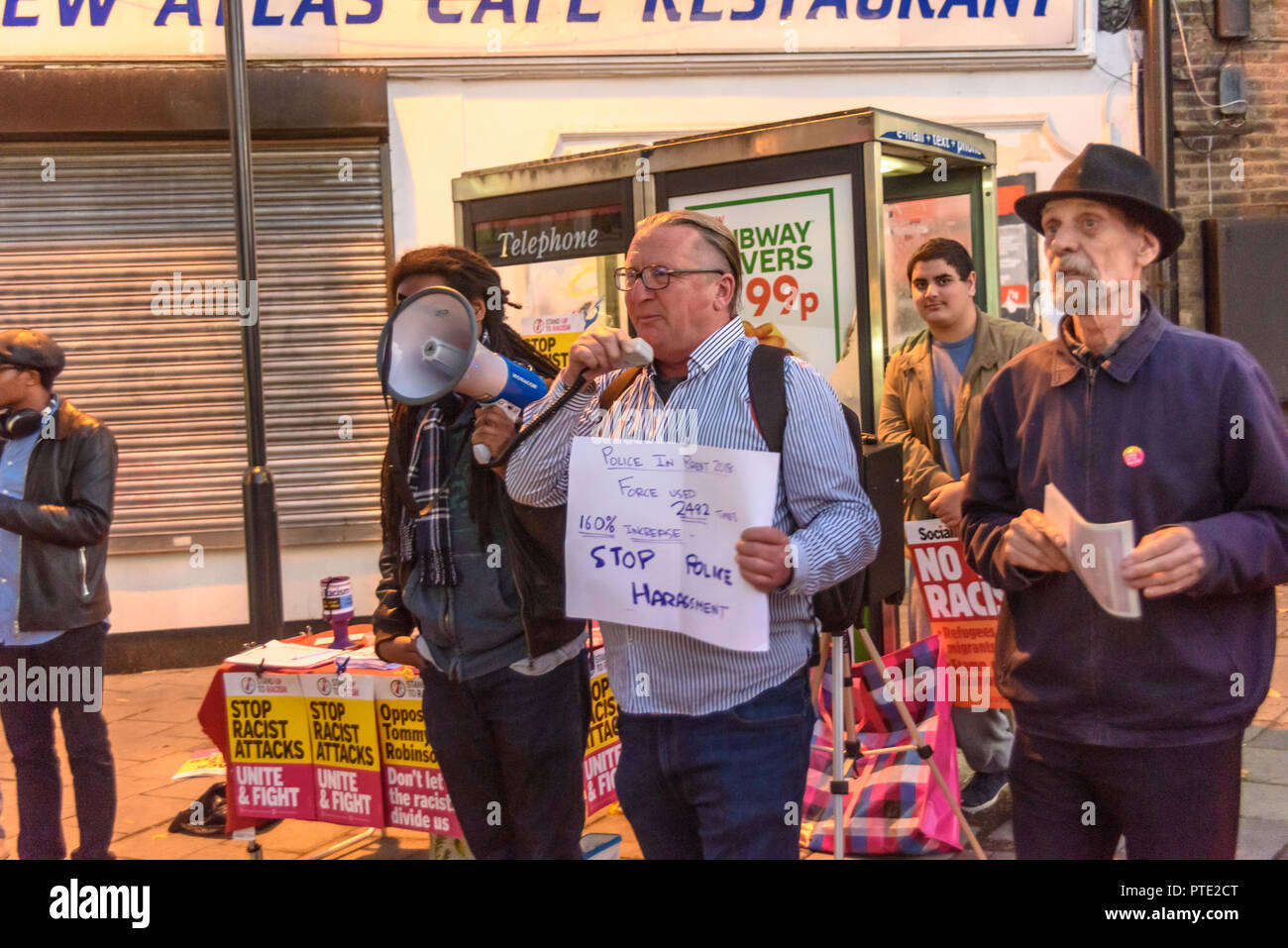 London, UK. October 9th 2018. A man holds a poster showing a huge increase in police use of force in Brent as he speaks about this at the rally outside the New Atlas Cafe Restaurant where a young black man was attacked by police who used obviously unnecessary force when arresting him on suspicion of having been involved in a knife attack. He was assaulted by six officers, and was viciously kicked while officers struggled to handcuff him, andwhen he was well under control and held on the ground he was sprayed in the face with CS gas. Credit: Peter Marshall/Alamy Live News - Stock Image