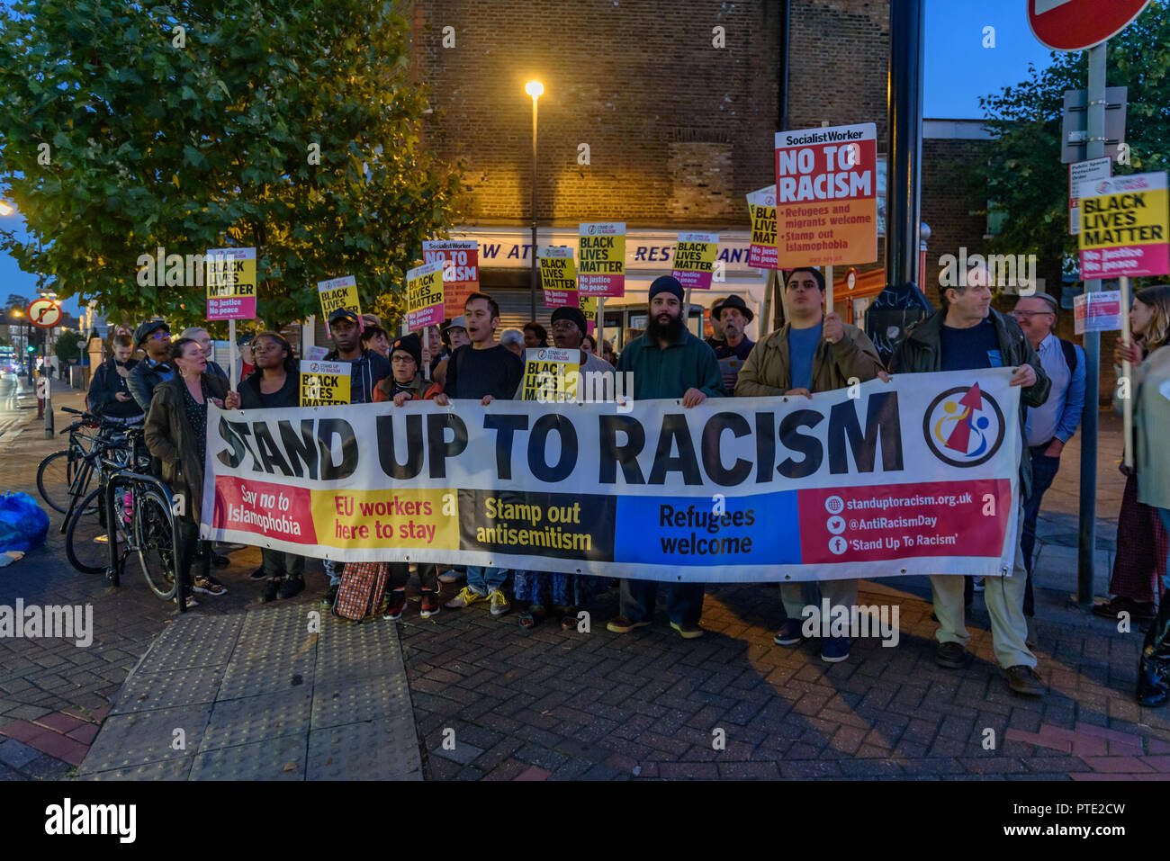London, UK. October 9th 2018. People pose behind the Stand Up to Racism banner at the rally outside the New Atlas Cafe Restaurant where a young black man was attacked by police who used obviously unnecessary force when arresting him on suspicion of having been involved in a knife attack. He was assaulted by six officers, and was viciously kicked while officers struggled to handcuff him, andwhen he was well under control and held on the ground he was sprayed in the face with CS gas. Credit: Peter Marshall/Alamy Live News - Stock Image