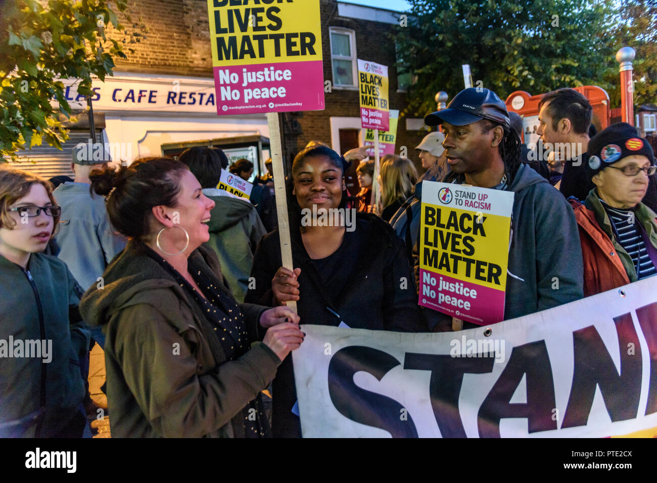 London, UK. October 9th 2018. People behind the Stand Up to Racism banner at the rally outside the New Atlas Cafe Restaurant where a young black man was attacked by police who used obviously unnecessary force when arresting him on suspicion of having been involved in a knife attack. He was assaulted by six officers, and was viciously kicked while officers struggled to handcuff him, andwhen he was well under control and held on the ground he was sprayed in the face with CS gas. Credit: Peter Marshall/Alamy Live News - Stock Image