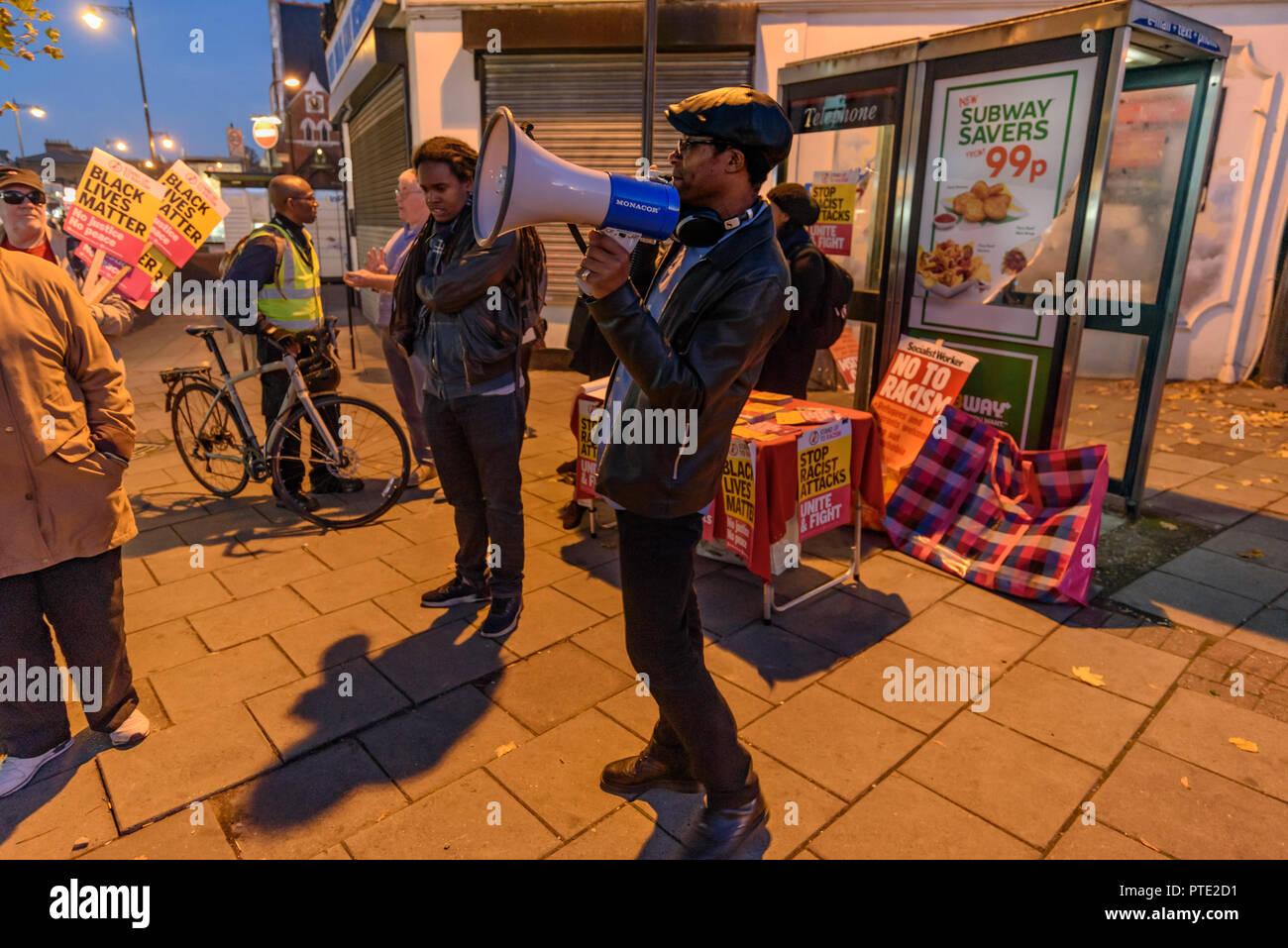 London, UK. October 9th 2018. Brian Richardson of Stand Up To Racism makes the final speech at the rally outside the New Atlas Cafe Restaurant where a young black man was attacked by police who used obviously unnecessary force when arresting him on suspicion of having been involved in a knife attack. He was assaulted by six officers, and was viciously kicked while officers struggled to handcuff him, andwhen he was well under control and held on the ground he was sprayed in the face with CS gas. Credit: Peter Marshall/Alamy Live News - Stock Image