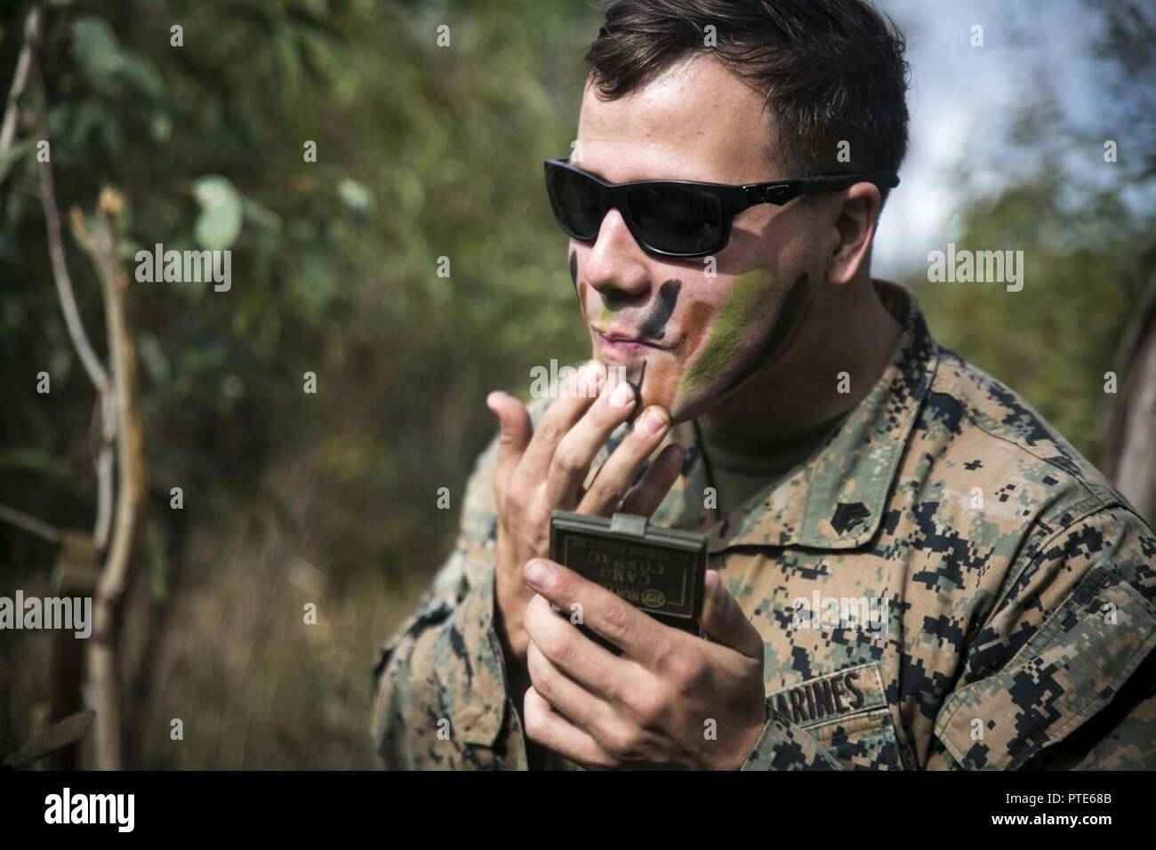 U.S. Marine Corps Sgt. Thomas J. Hudson, a squad leader with the 1st Platoon, India Company, Battalion Landing Team, 3rd Battalion, 5th Marines, 31st Marine Expeditionary Unit, applies camouflage paint during Exercise Talisman Saber 17 in the Australia Defense Force's Townshend Island Training Area, Queensland, Australia, July 14, 2017. The company's simulated mission included clearing and securing the training area. India Company is the mechanized raid company for the 31st MEU, currently supporting Talisman Saber 17 while deployed on its scheduled patrol of the Indo-Asia-Pacific region. Talis - Stock Image