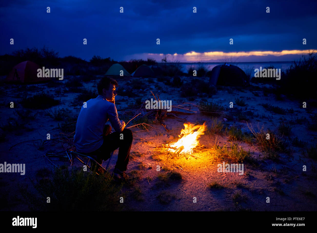 Man looking at campfire and tent at night on the lake beach Stock Photo