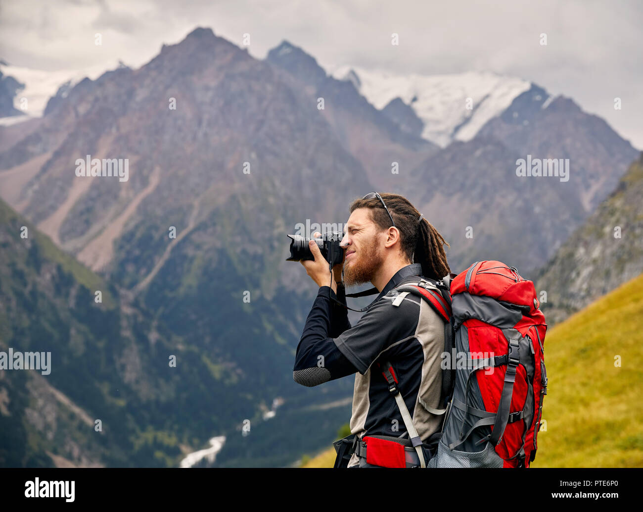 Man photographer with big backpack and camera taking photo of the mountains. Travel Lifestyle concept adventure active vacations outdoor - Stock Image