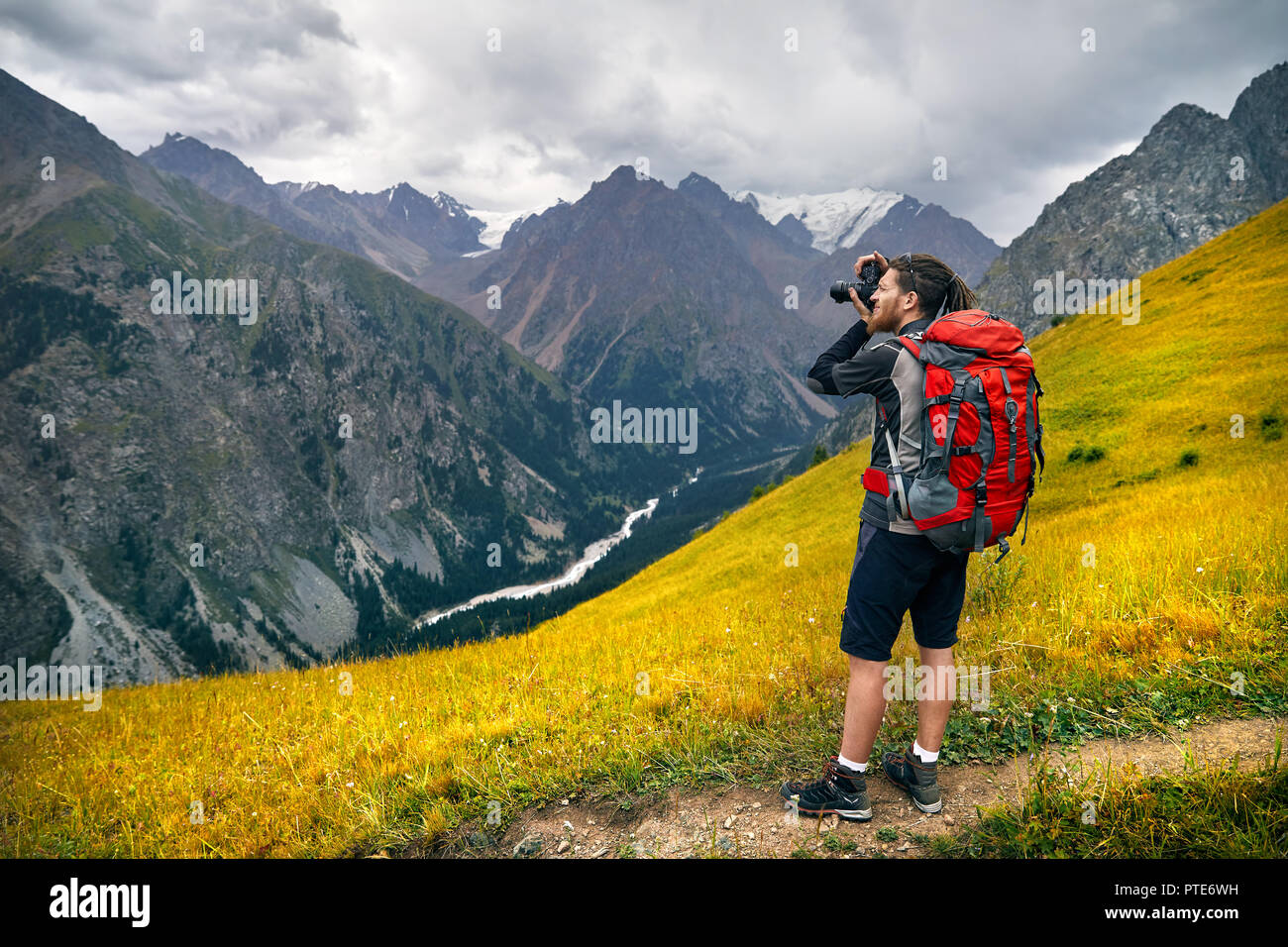 Man photographer with big backpack and camera taking photo in the mountains. Travel Lifestyle concept adventure active vacations outdoor - Stock Image