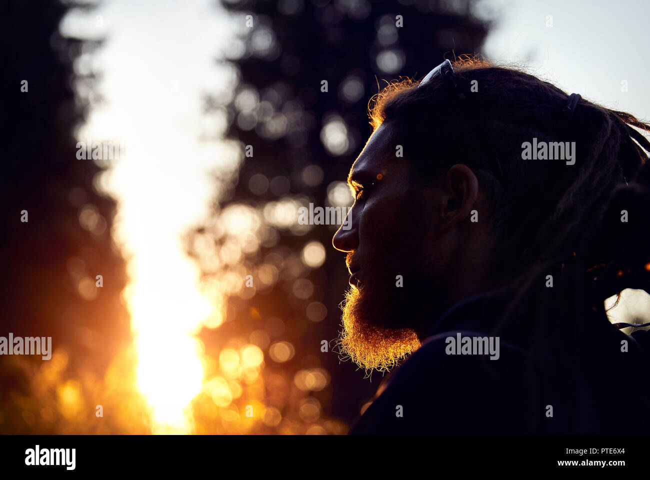 Man silhouette with dreadlocks in sunset mountain forest - Stock Image