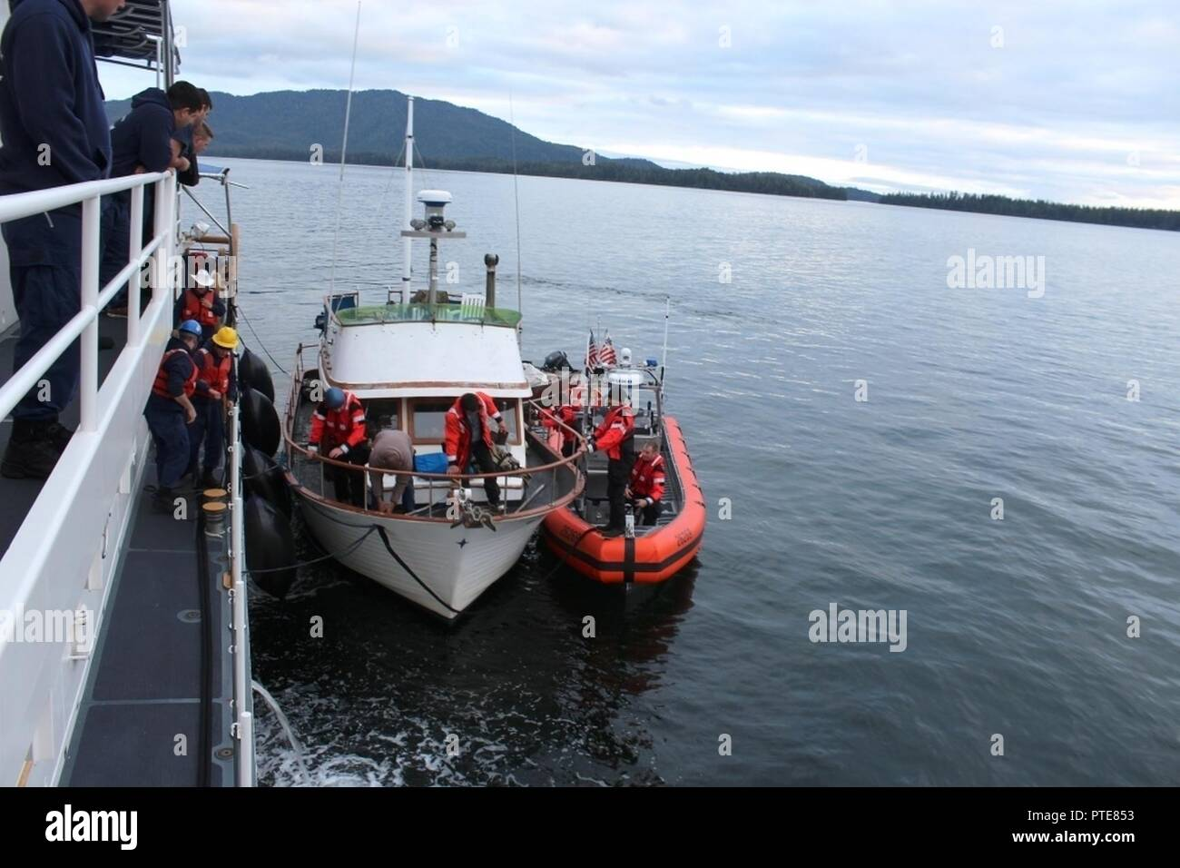 A Coast Guard small-boat crew transfers tow of the 36-foot vessel Viking Queen to the Cutter John McCormick in Elena Bay, 50 miles southwest of Kake, Alaska, July 16, 2017. The crew of the John McCormick and a Kake Search and Rescue crew responded to the vessel after it became disabled and stranded. - Stock Image