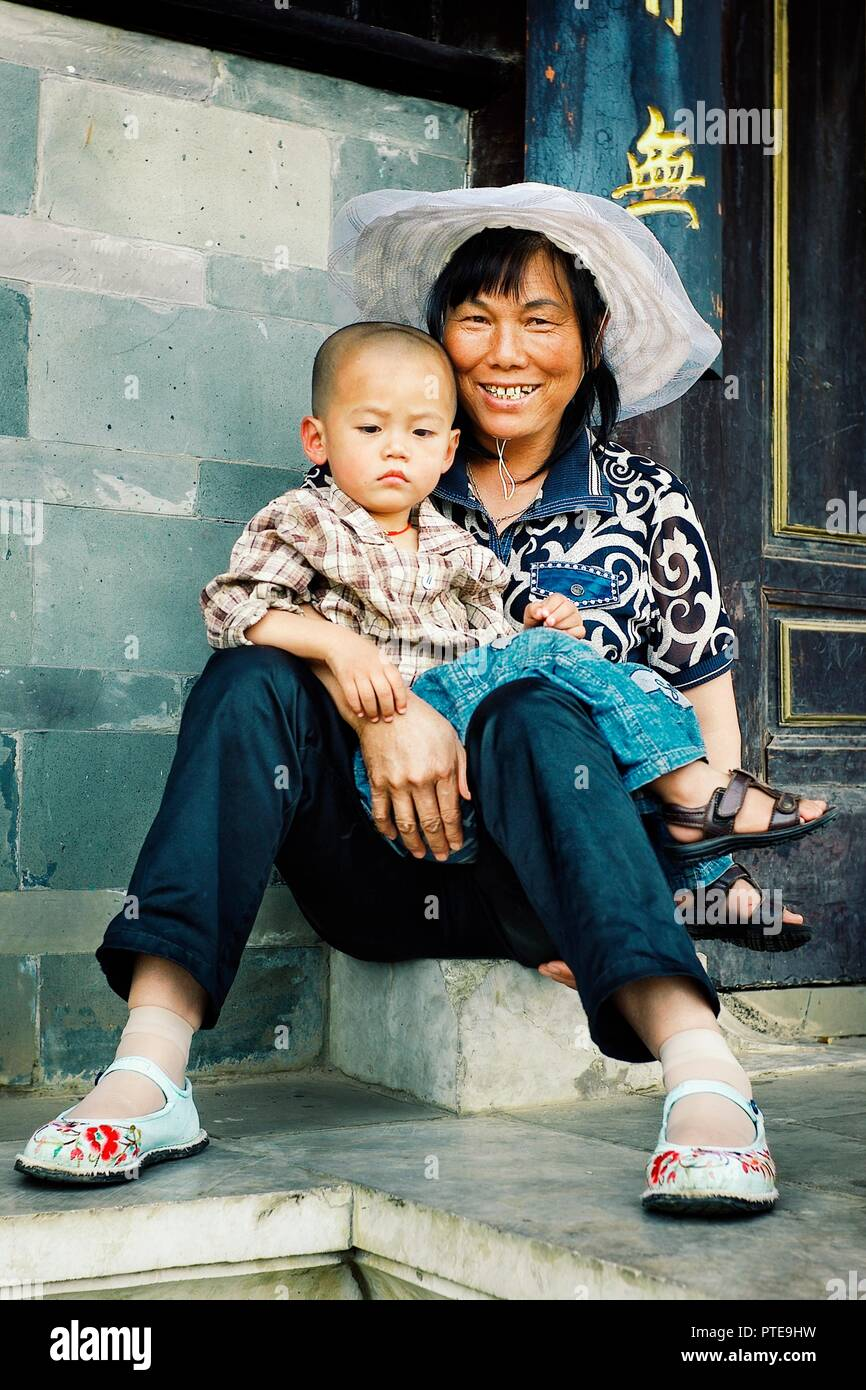 Beijing / China - JUN 24 2011: young mother with her kid in front of the gates of a temple Stock Photo
