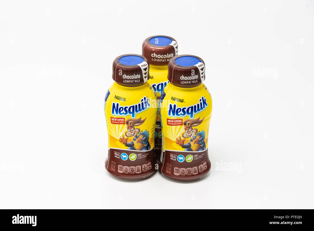 Portland, OR / USA - October 8 2018: Three Nesquik by Nestle company chocolate milk bottles with drink for kids on light background - Stock Image