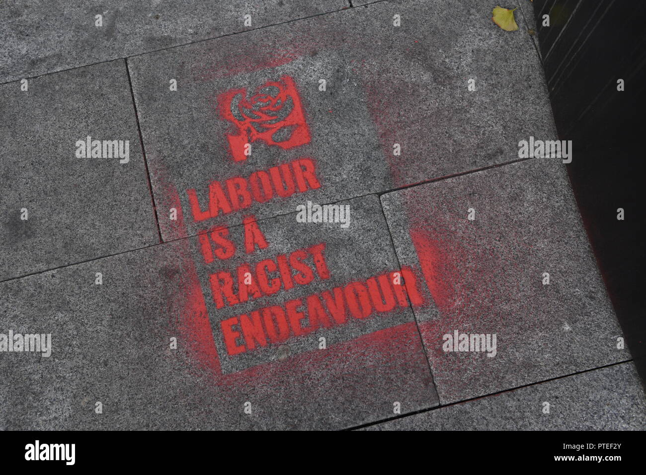Labour is a racist endeavour - stencil sprayed on a pavement outside the Labour Party Conference 2018 in Liverpool, England, UK - Stock Image