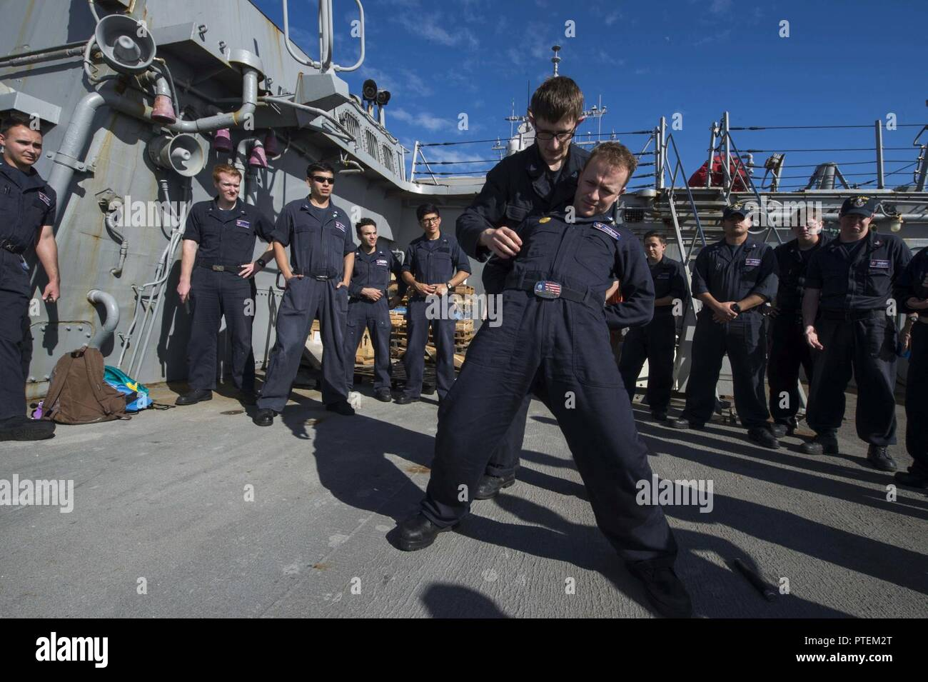Fire Controlman 3rd Class Tyler Weathers, assigned to the forward-deployed Arleigh Burke-class guided-missile destroyer USS Barry (DDG 52), pats down Master-at-Arms 1st Class Nicholas Whitman as part of security reactionary forces training. - Stock Image