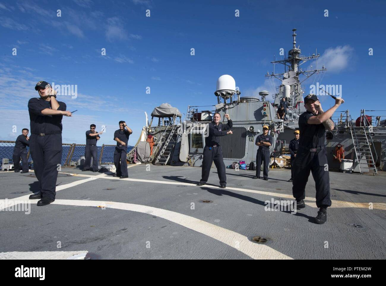Sailors assigned to the forward-deployed Arleigh Burke-class guided-missile destroyer USS Barry (DDG 52), practice striking with a baton as part of security reactionary forces training. - Stock Image