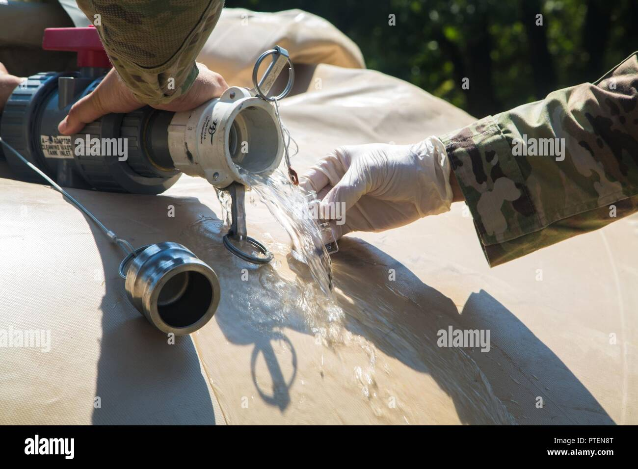 U.S. Army Sgt. Joshua Holtsberg, assigned 21st TSC (Theater Sutainment Command), 30th Medical Brigade, 421st MMB (Medical Multifunctional Battalion), 71st Medical Detachment, pours water into a test tube as part of a water inspection at Novo Selo, Bulgaria, July 15, 2017. Saber Guardian 17 is a multinational readiness exercise where 22 countries gather to build partnership and a stronger Europe. - Stock Image