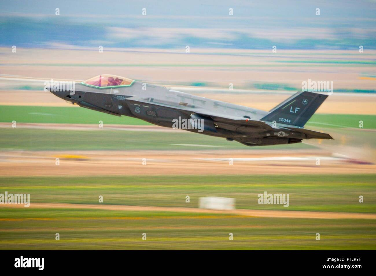 A 56th Fighter Wing F-35A Lightning II pilot takes off from Luke Air Force Base, Ariz., July 17, 2017. F-35 basic course students took part in a two and a half week, four flight phase replicating a wartime environment designed to test their training and skills. Today's flight featured six F-35's facing off against eight F-16 Fighting Falcons in defensive counter air attack operation measures. The students will be the first ever to graduate from a course designed specifically to utilize the mission set of the F-35. - Stock Image