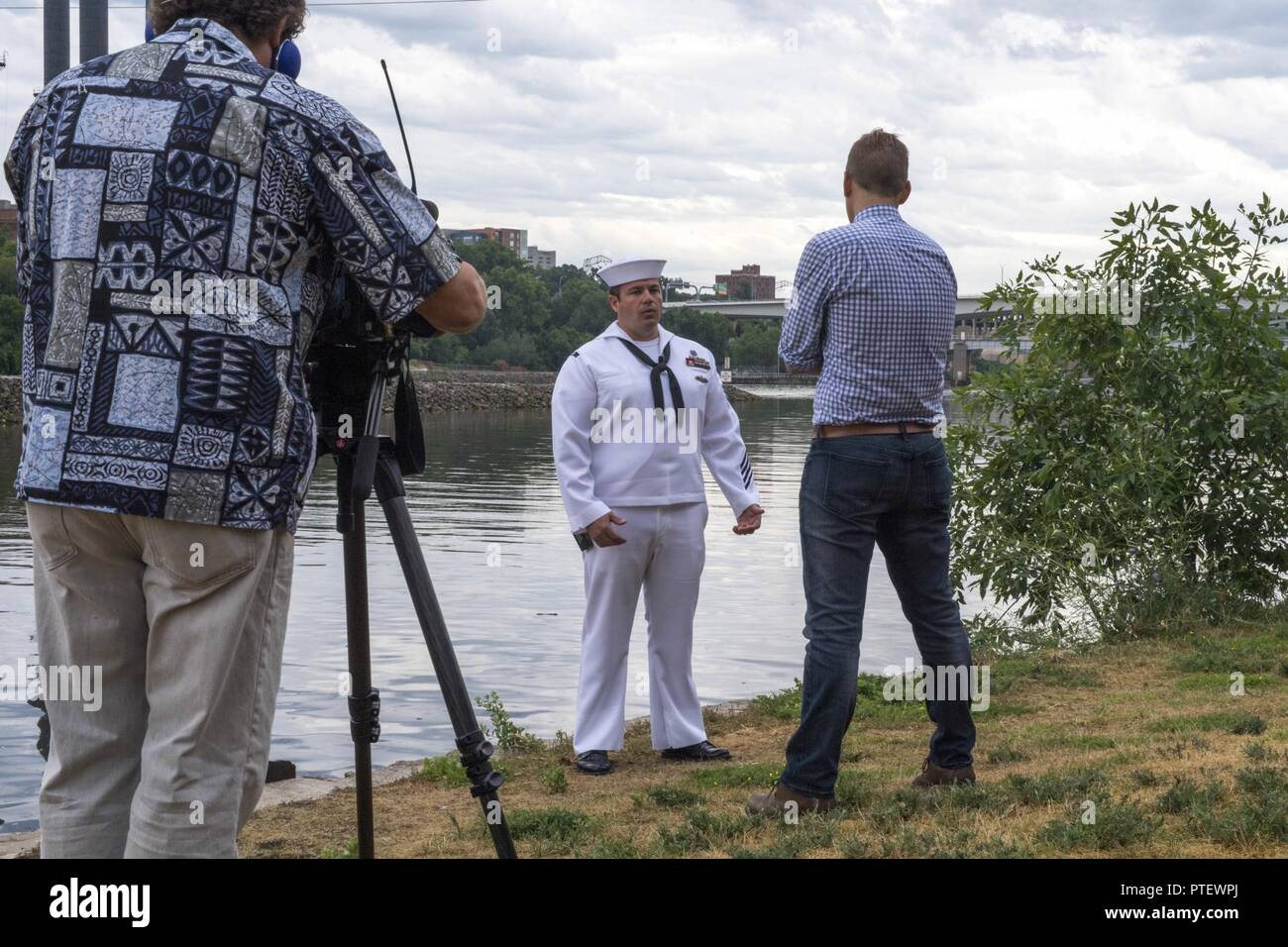 MINNEAPOLIS (July 18, 2017) –Navy Diver 1st Class Brian Bennett is interviewed on the bank of the Mississippi River by NBC KARE 11 reporter Kent Erdahl, near the site of the collapse of the I-35W bridge ten years ago, where Bennett was called to assist local, state and federal authorities in finding missing victims, while he was attached to Mobile Diving and Salvage Unit (MDSU) 2. Bennett returned to the area to take part in a wreath laying ceremony during Minneapolis/St. Paul Navy Week, which recognized those who responded to the tragedy and remembered those lost. Navy Week programs serve as  - Stock Image