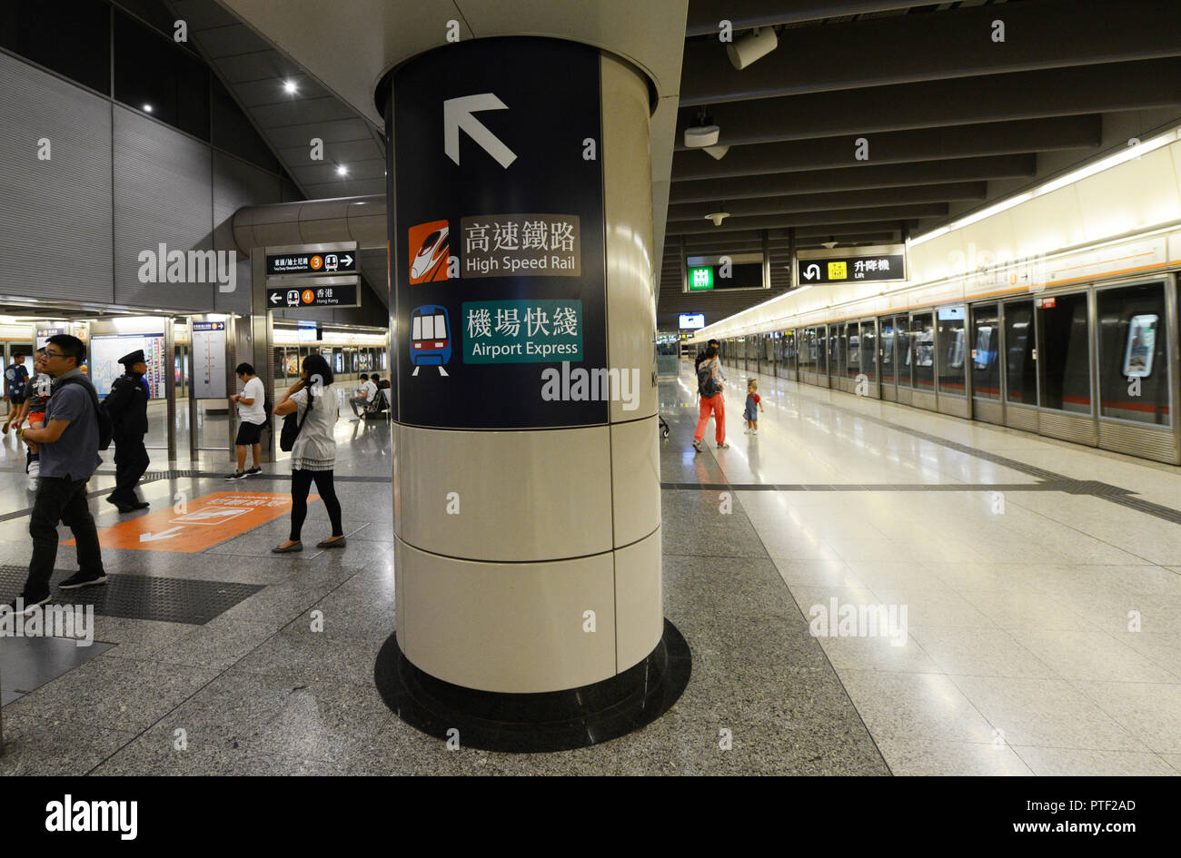 Passengers waiting for The Tung Chung line in Hong Kong station. - Stock Image