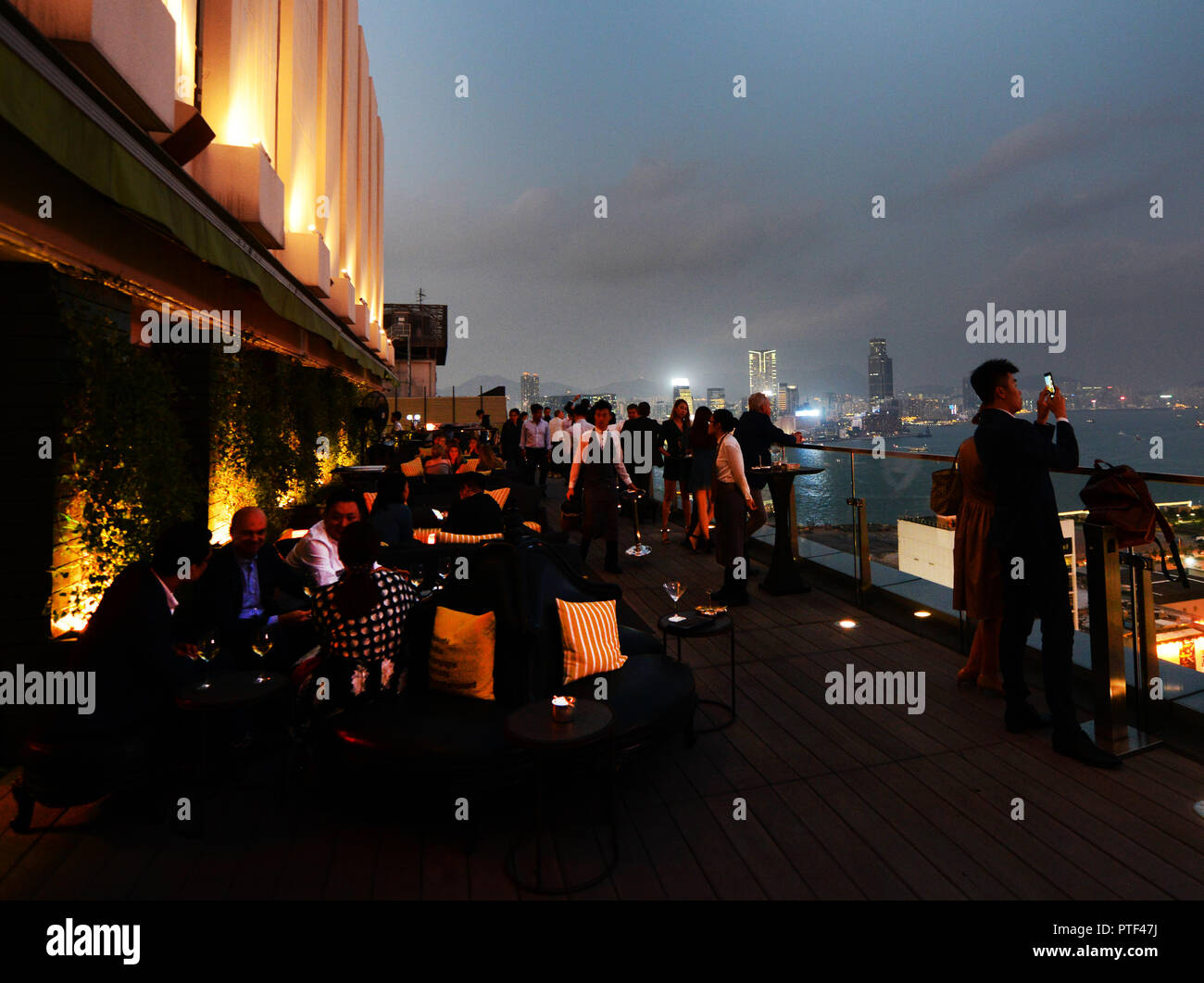 Enjoying cocktails and drinks with the fabulous views of Hong Kong. - Stock Image