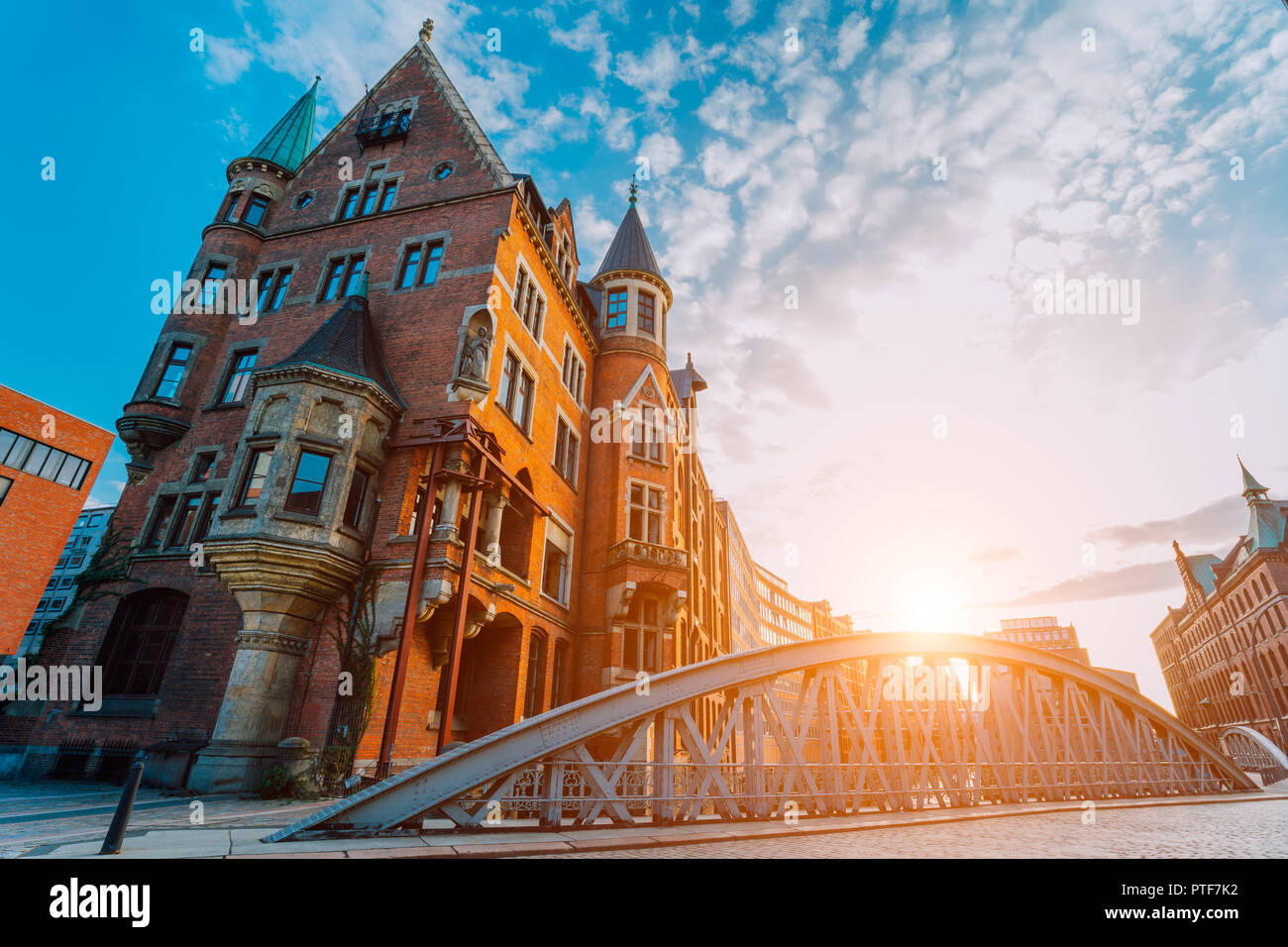 Metal arch bridge and old red bricks building in the Speicherstadt warehouse district of Hamburg HafenCity with sunburst light during sunset golden hour and white clouds against blue sky above - Stock Image